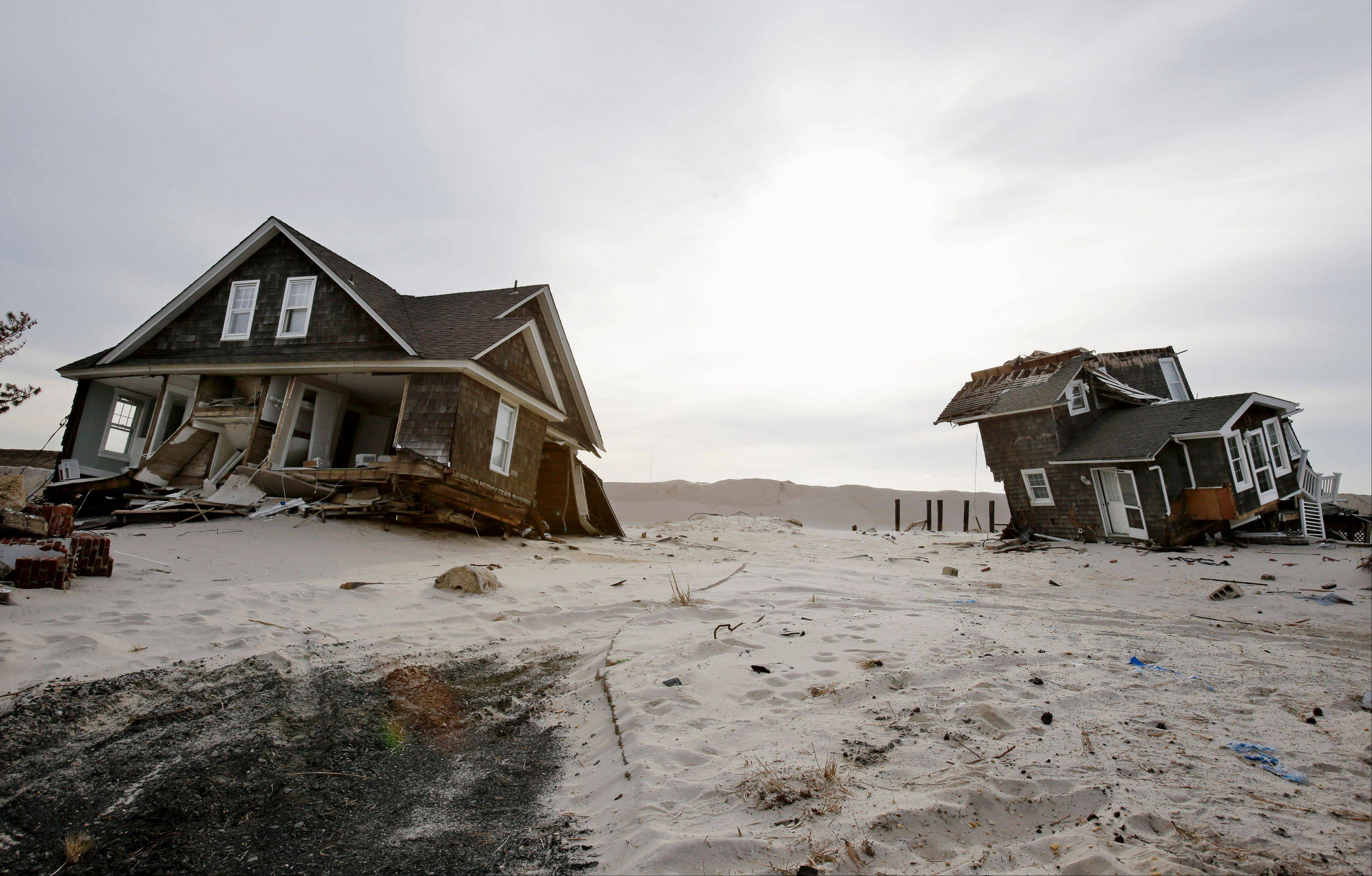This Feb. 22, 2013, file photo shows Two heavily damaged homes on the beach in Mantoloking, N.J., from Superstorm Sandy. Man-made global warming may decrease the likelihood of the already unusual steering currents that pushed Superstorm Sandy due west into New Jersey in a freak 1-in-700 year path, researchers report.