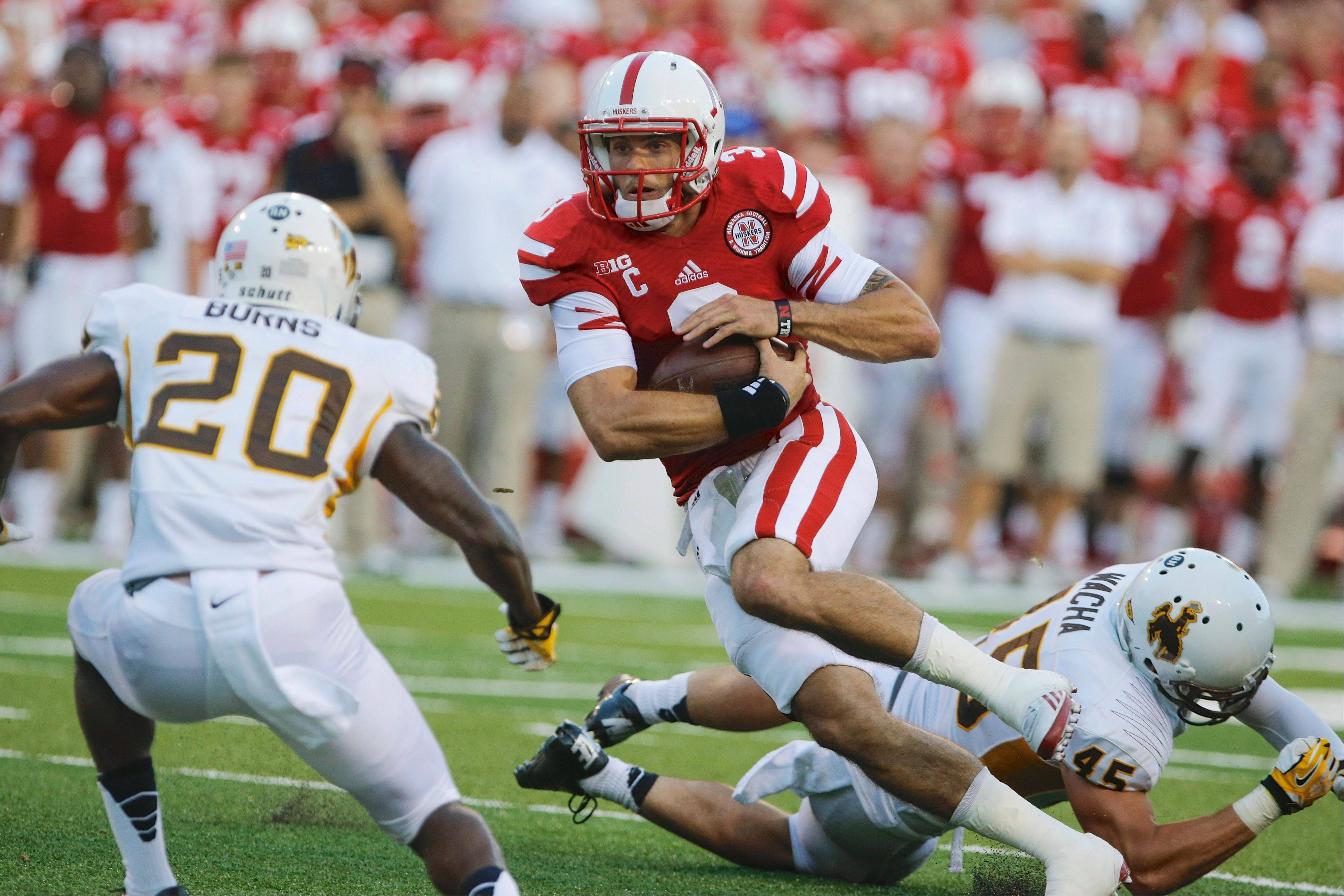 Nebraska quarterback Taylor Martinez carries the ball past Wyoming linebacker Lucas Wacha, right, and cornerback Blair Burns in the first half of Saturday�s game in Lincoln.