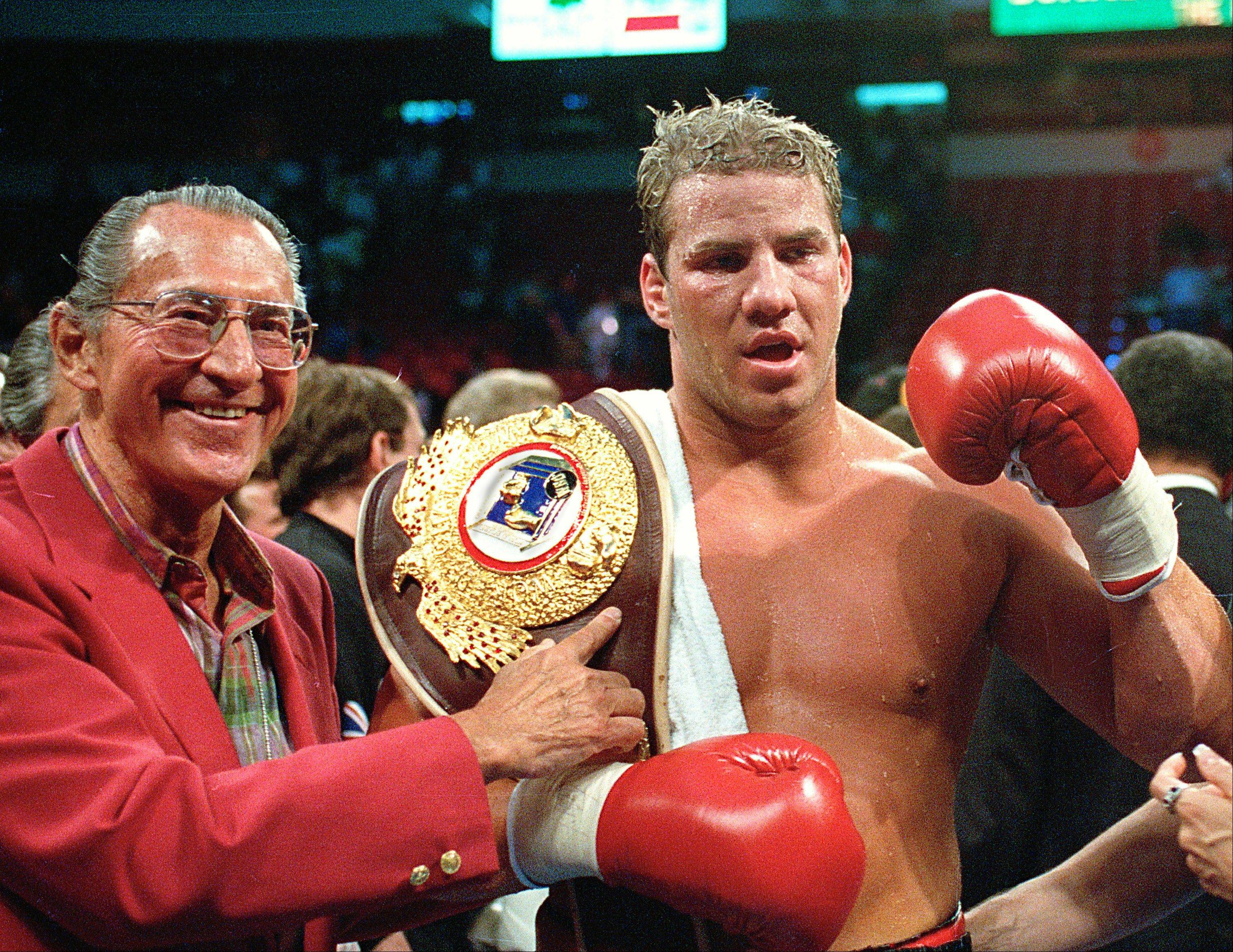In this June 7, 1993 file photo, newly crowned WBO heavyweight champion Tommy Morrison receives his championship belt after defeating George Foreman in Las Vegas, Nev. Morrison, a former heavyweight champion who gained fame for his role in the movie �Rocky V,� has died. He was 44. Morrison�s former manager, Tony Holden says his longtime friend died Sunday night, Sept. 1, 2013, at a Nebraska hospital.