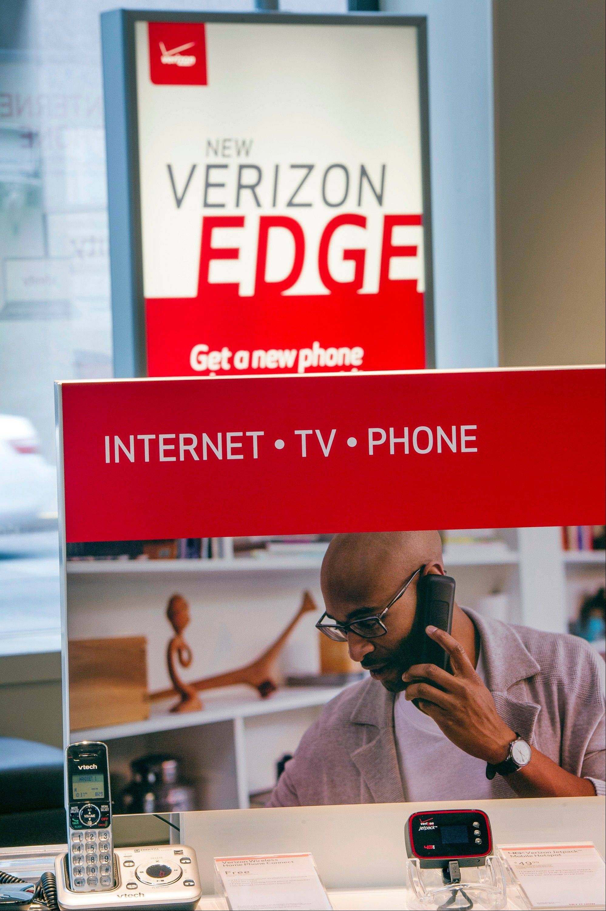 Verizon Wireless signage is displayed with products inside the company's store in San Francisco, California, U.S. on Thursday Aug. 29, 2013. Verizon Communications Inc.'s buyout of the rest of its wireless venture may yield more than $240 million in fees for the bankers lucky enough to win a role on the biggest transaction in more than a decade.