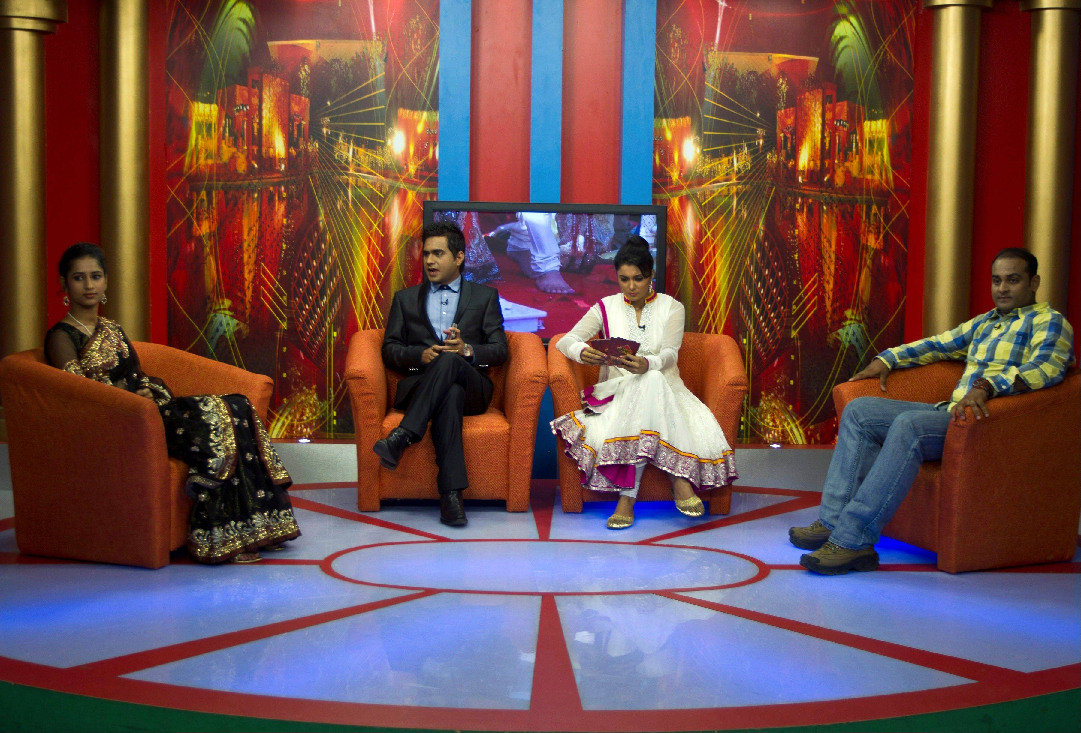 "In this July 26, 2013 photo, Nidhi Gaur, far left and her fiance Rahul Rai, far right, participate in ""So It's Final,"" a talk show on Shagun TV that features engaged couples in Noida, India. Indians are obsessed with weddings and obsessed with reality television."