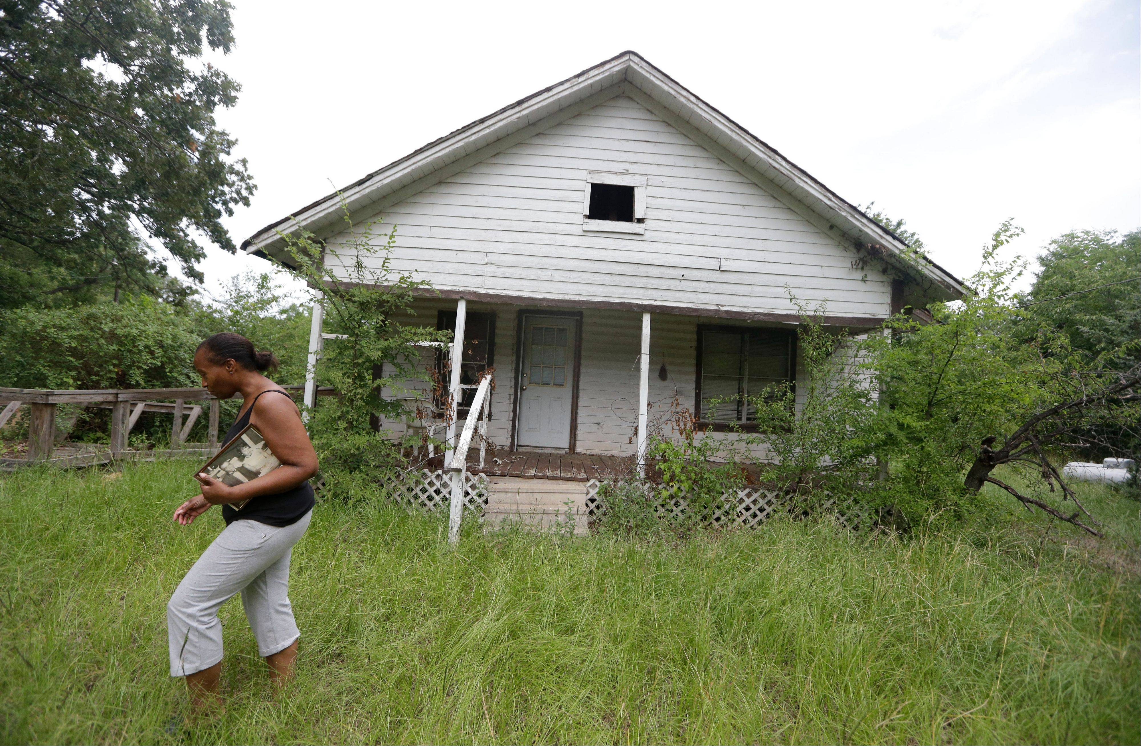 Jacquelin Finley carries a family photo she recovered during a visit to the house she grew up in with her family in Dirgin, Texas. The Finleys are descendants from slaves, and are fighting to keep a mining company from taking over land once owned by their ancestors.