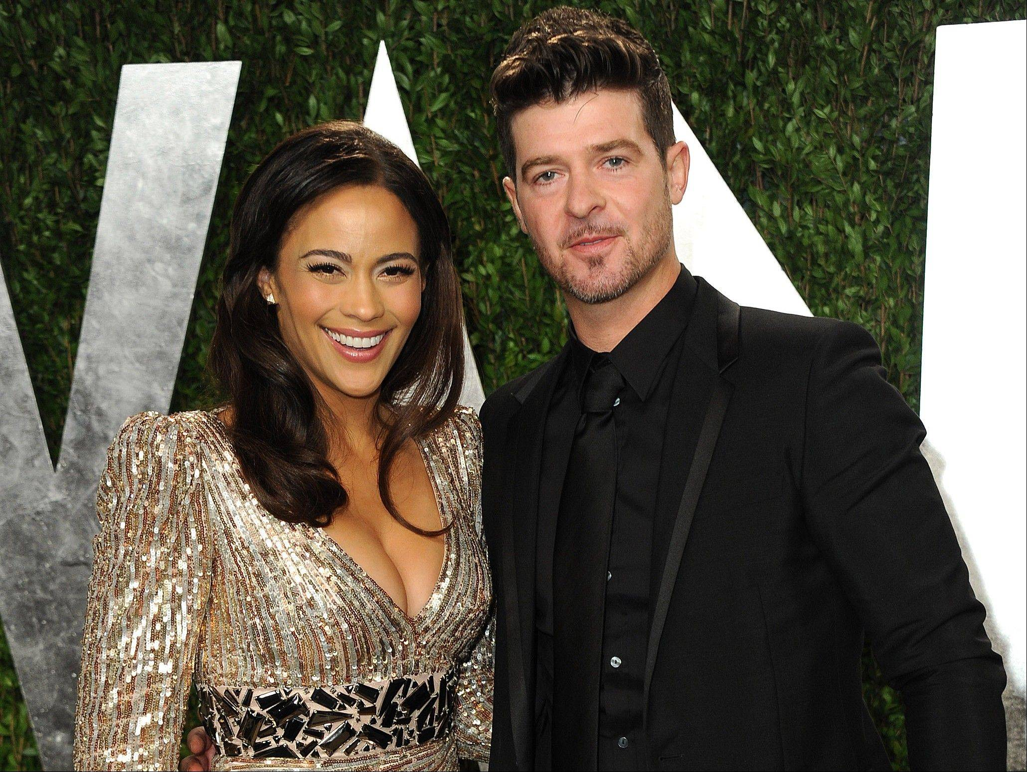 FILE - In this Feb. 24, 2013 file photo, Paula Patton and Robin Thicke arrive at the 2013 Vanity Fair Oscars Viewing and After Party at the Sunset Plaza Hotel in West Hollywood, Calif. Patton is busy promoting her second film this year, the upcoming romantic comedy �Baggage Claim.� Personally, Patton is relishing the success of her recording artist husband Thicke, whose catchy summer hit �Blurred Lines� has topped Billboard's Hot 100 chart. (Photo by Jordan Strauss/Invision/AP, File)