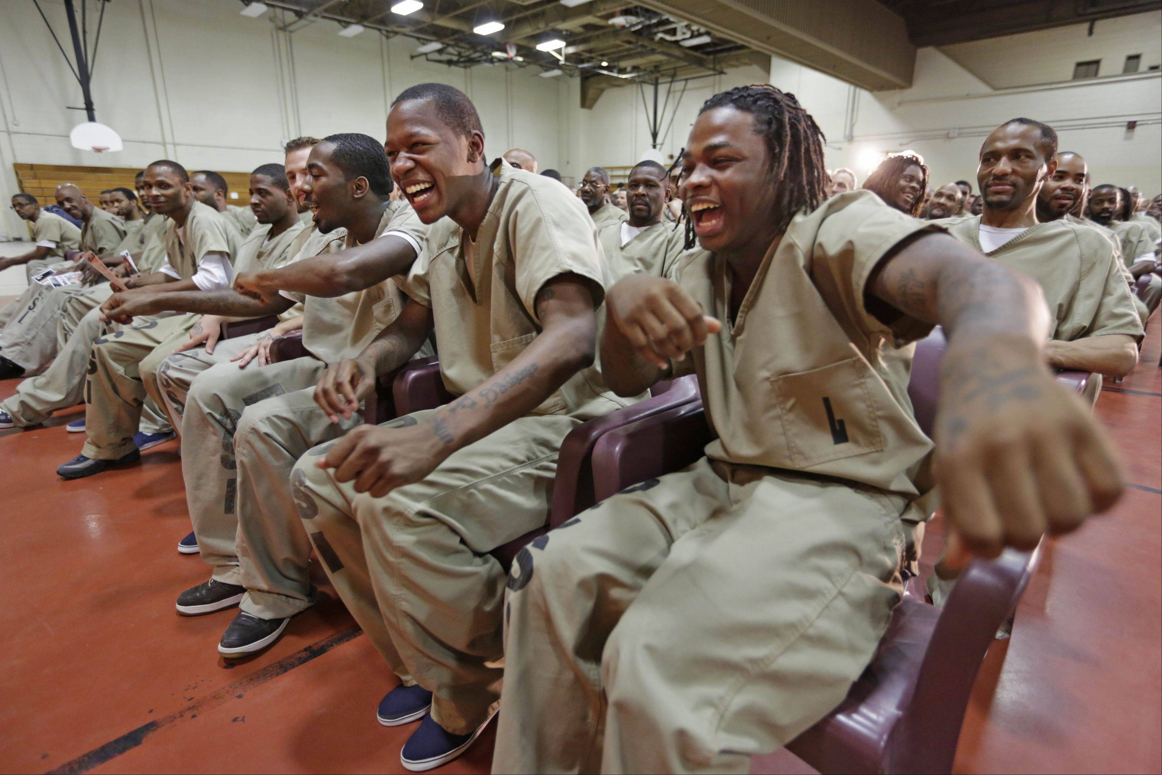 "Inmates, from left, Eric McNeil, Kevin Fields and Julian Campbell, dance in their seats while watching rappers perform a hip hop adaptation of William Shakespeare's Othello, titled ""Othello: The Remix"" at the Cook County Jail in Chicago."