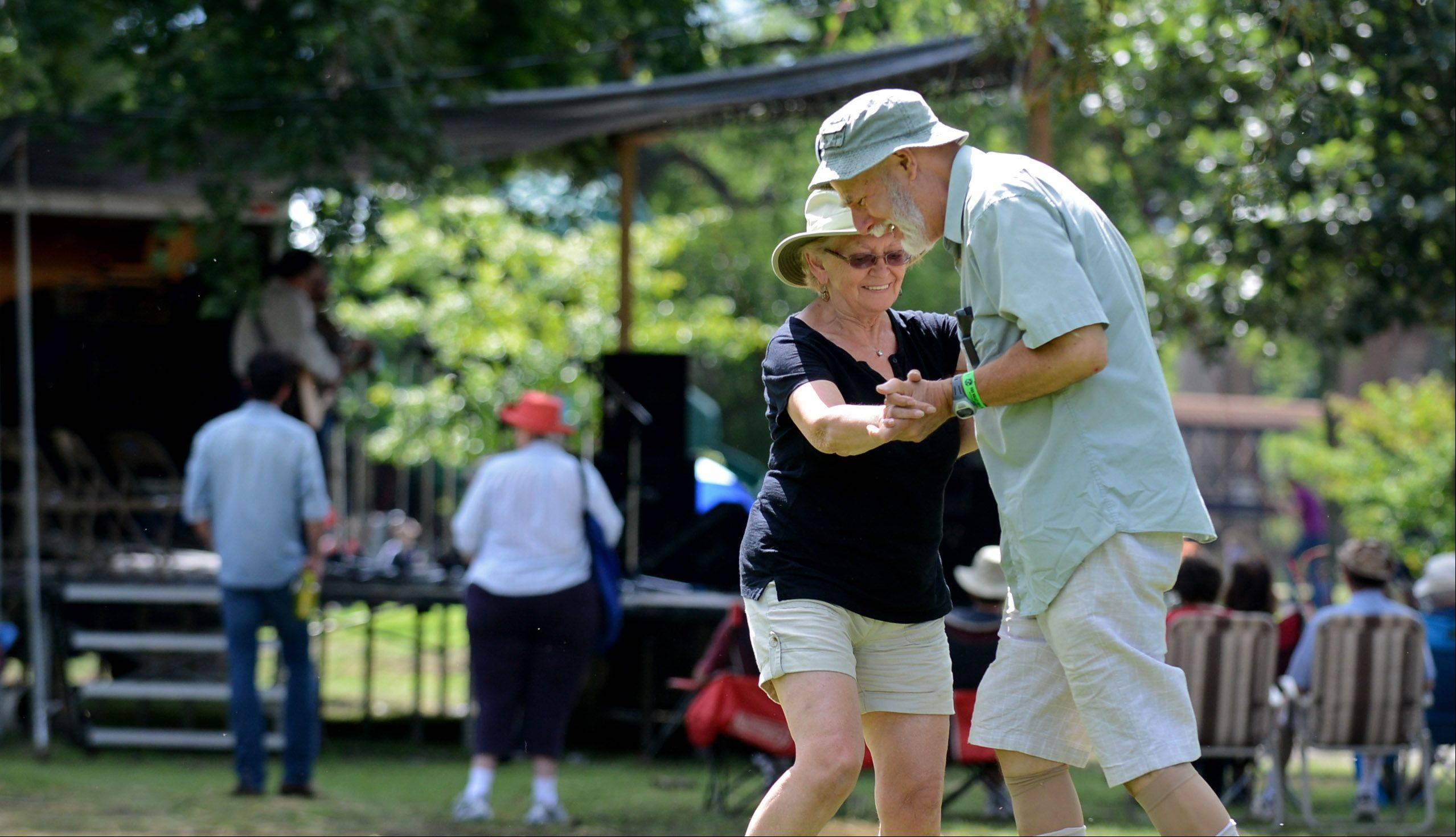 "Margaret Mantle and Elliot Zashin of Evanston share a dance while enjoying the sounds of Dennis Stroughmatt & Creole Spirit on Monday during the 37th annual Fox Valley Folk Music and Storytelling Festival at Island Park in Geneva. ""We love this festival and we especially love the Cajun music,"" Mantle said."
