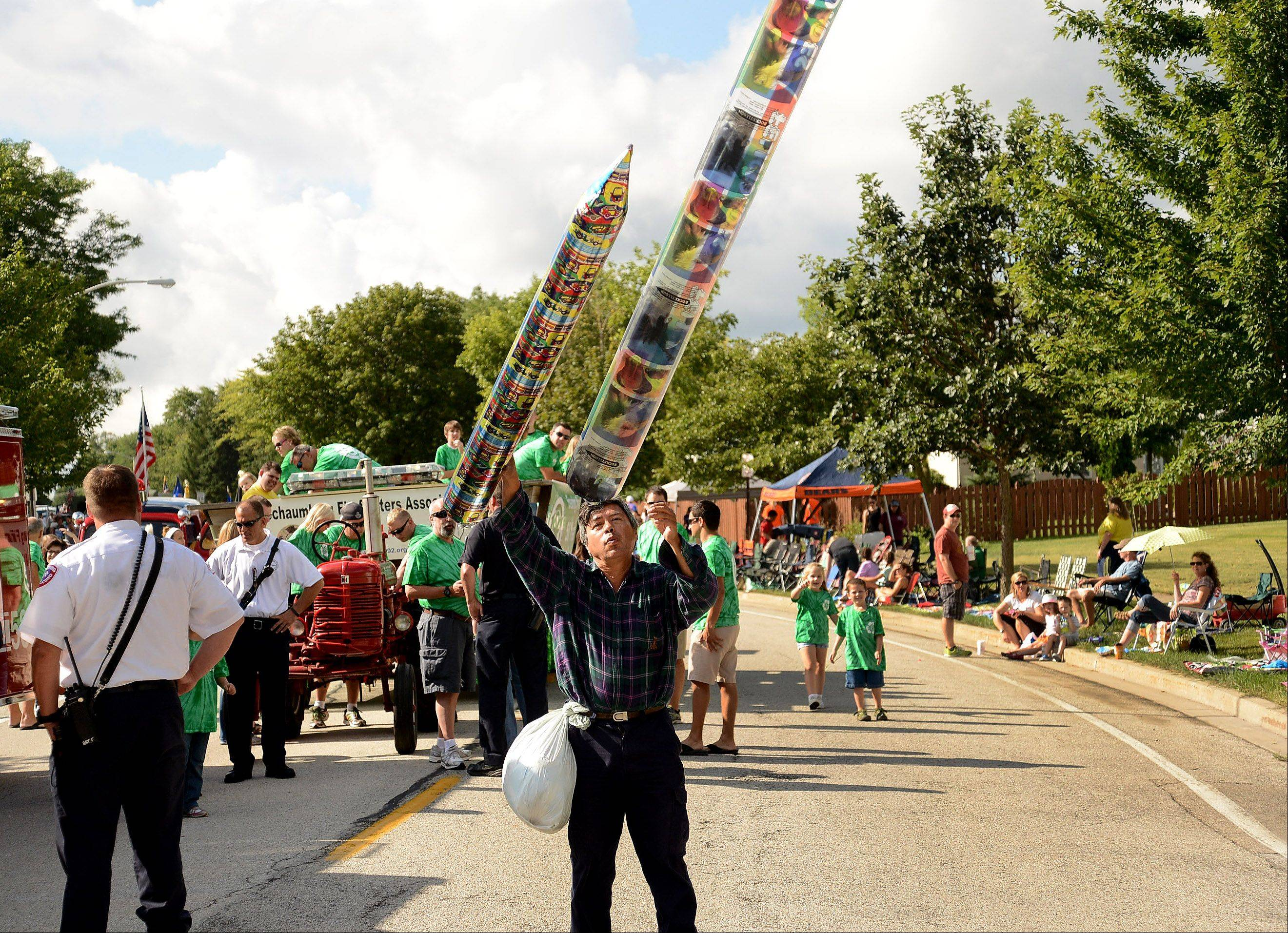 Eugenio Marin launches his cylindrical balloons during the annual Schaumburg Septemberfest parade Monday.