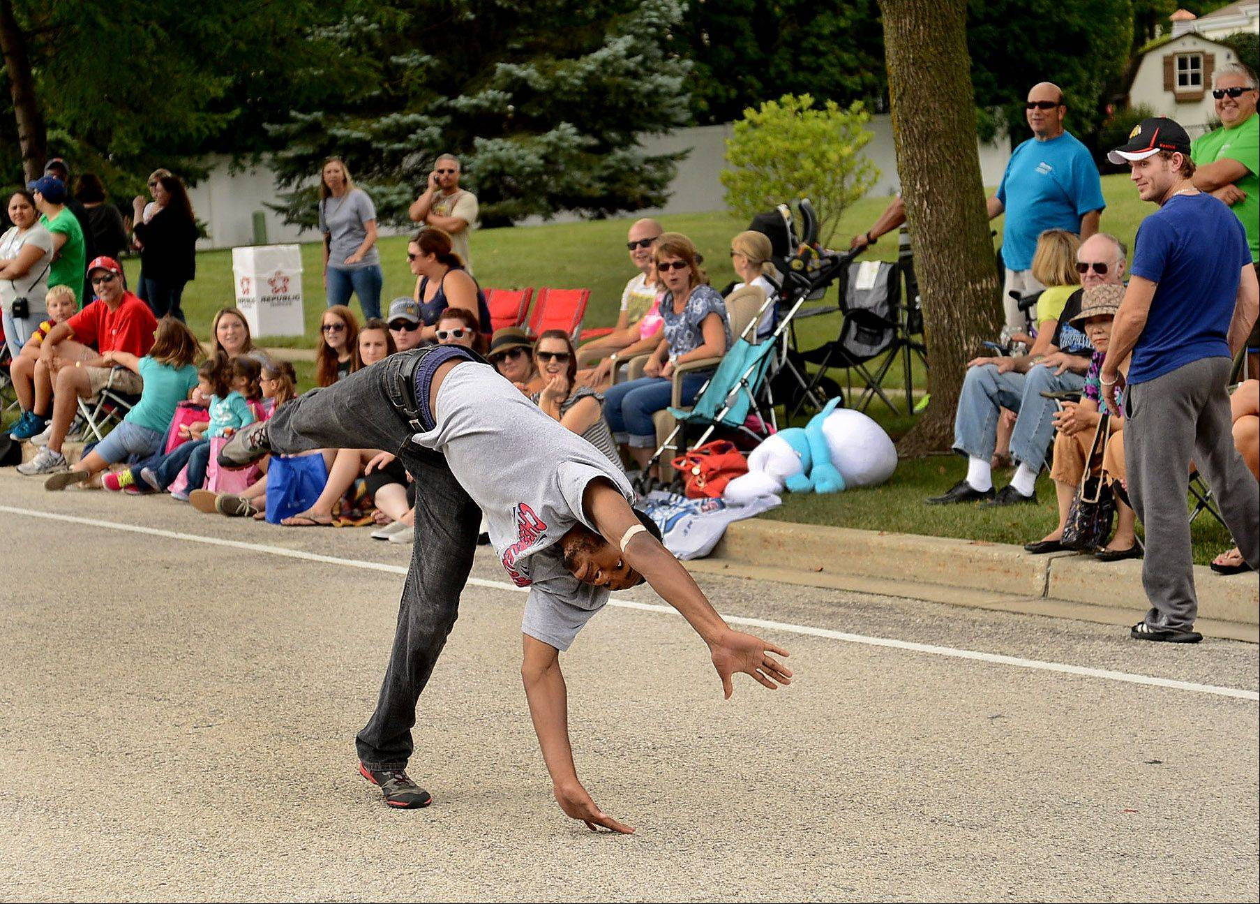 Former Conant cheerleader Rico Ludington does some gymnastics moves along the parade route during the annual Schaumburg Septemberfest parade on Monday.