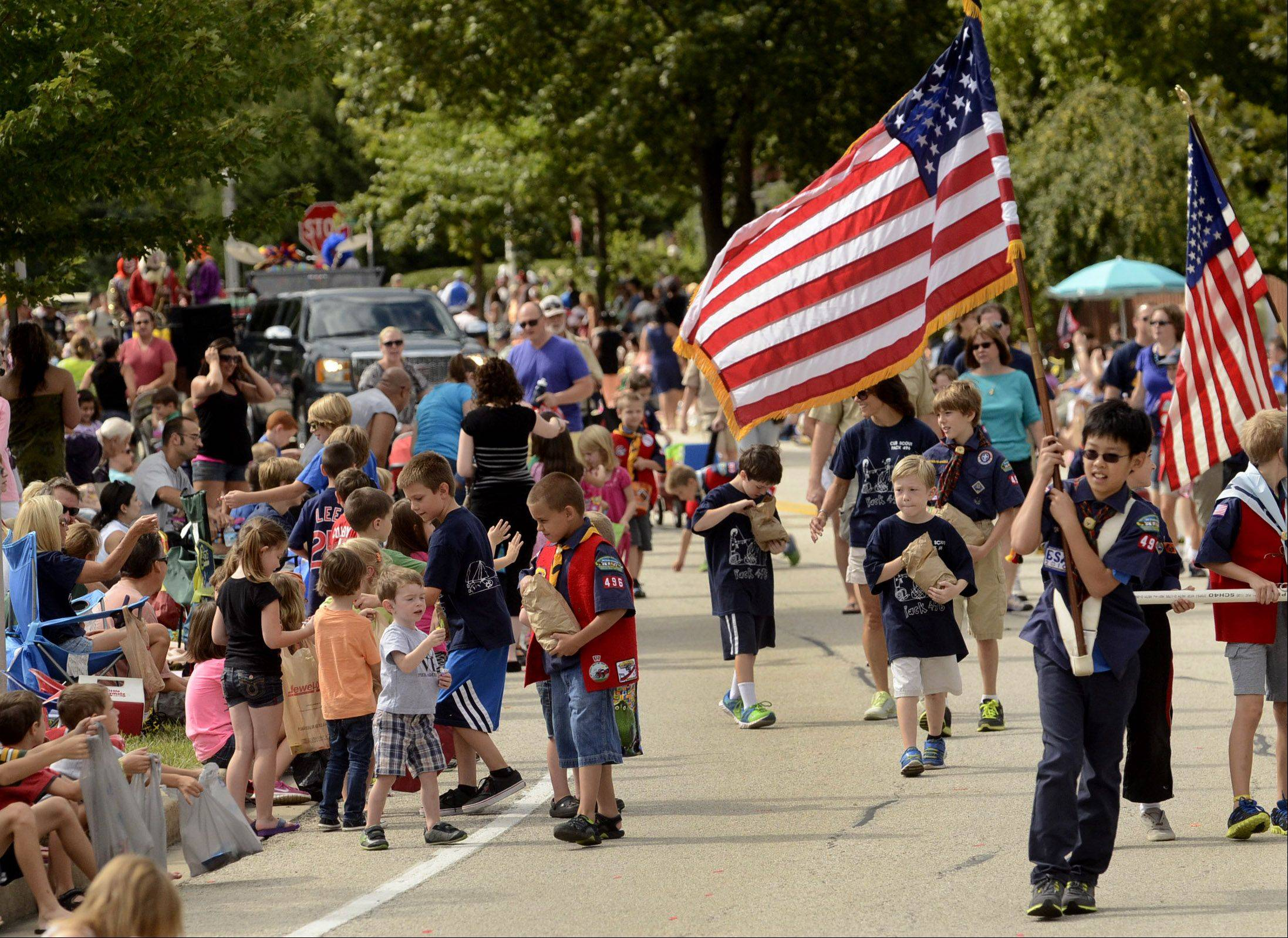 Evan Lee, right, of Cub Scout Pack 496 marches with the American flag during the annual Schaumburg Septemberfest parade.