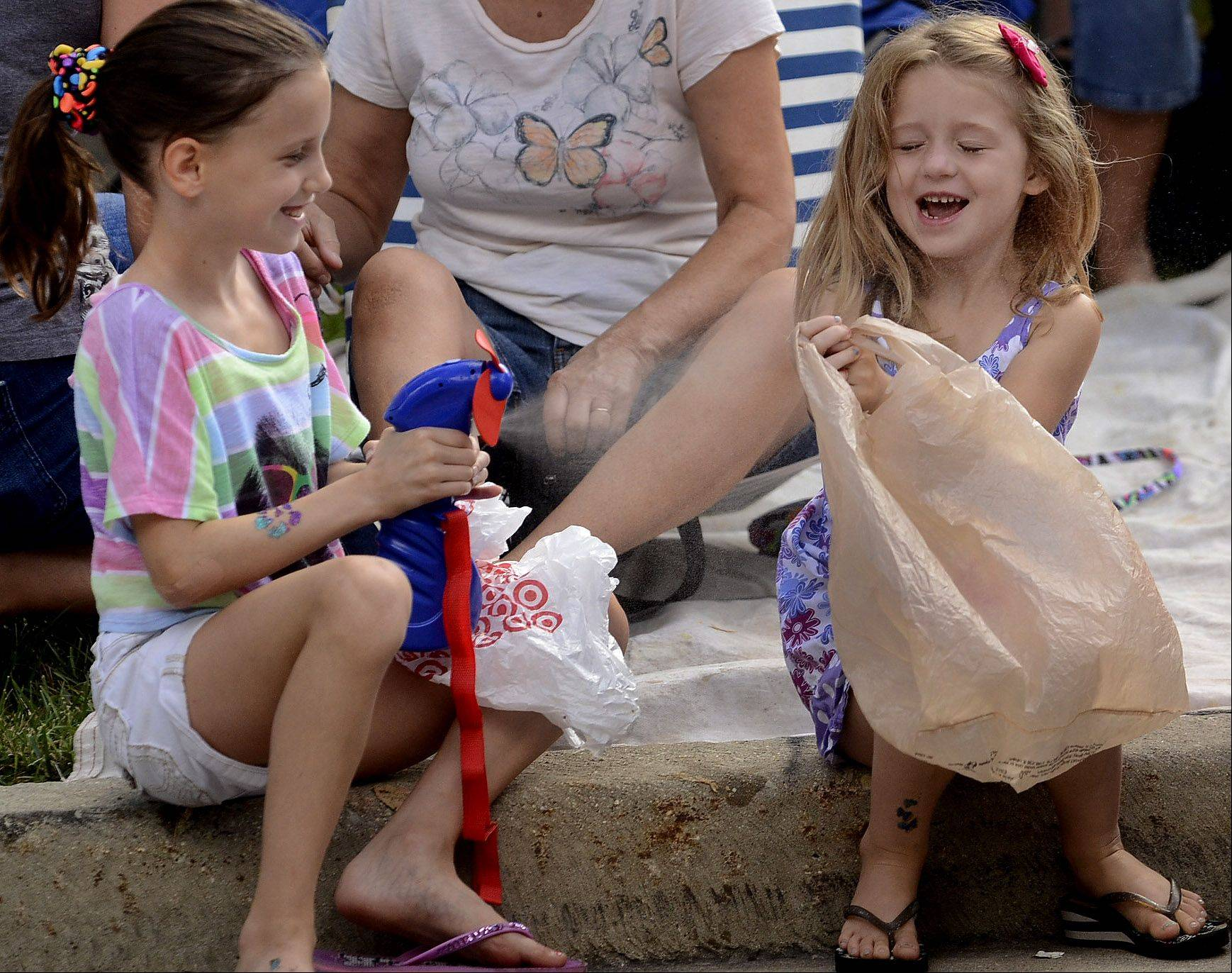 Teagan Larsen, left, squirts Dani Arnold with a mister while cooling off Monday during the annual Schaumburg Septemberfest parade.