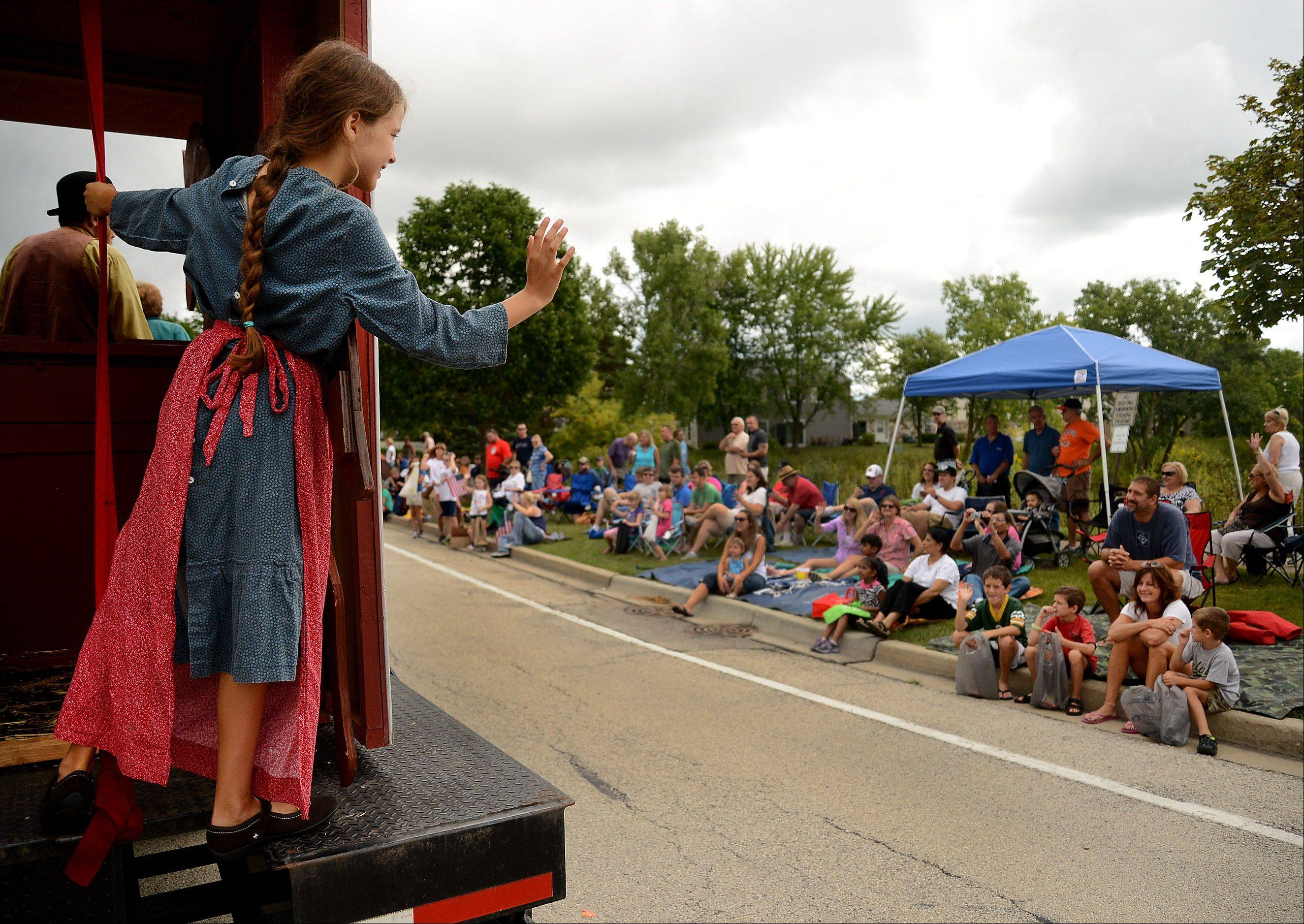 Sophia Holmes, riding the Spring Valley Nature Center float, waves to the crowd along the Septemberfest parade route in Schaumburg Monday.