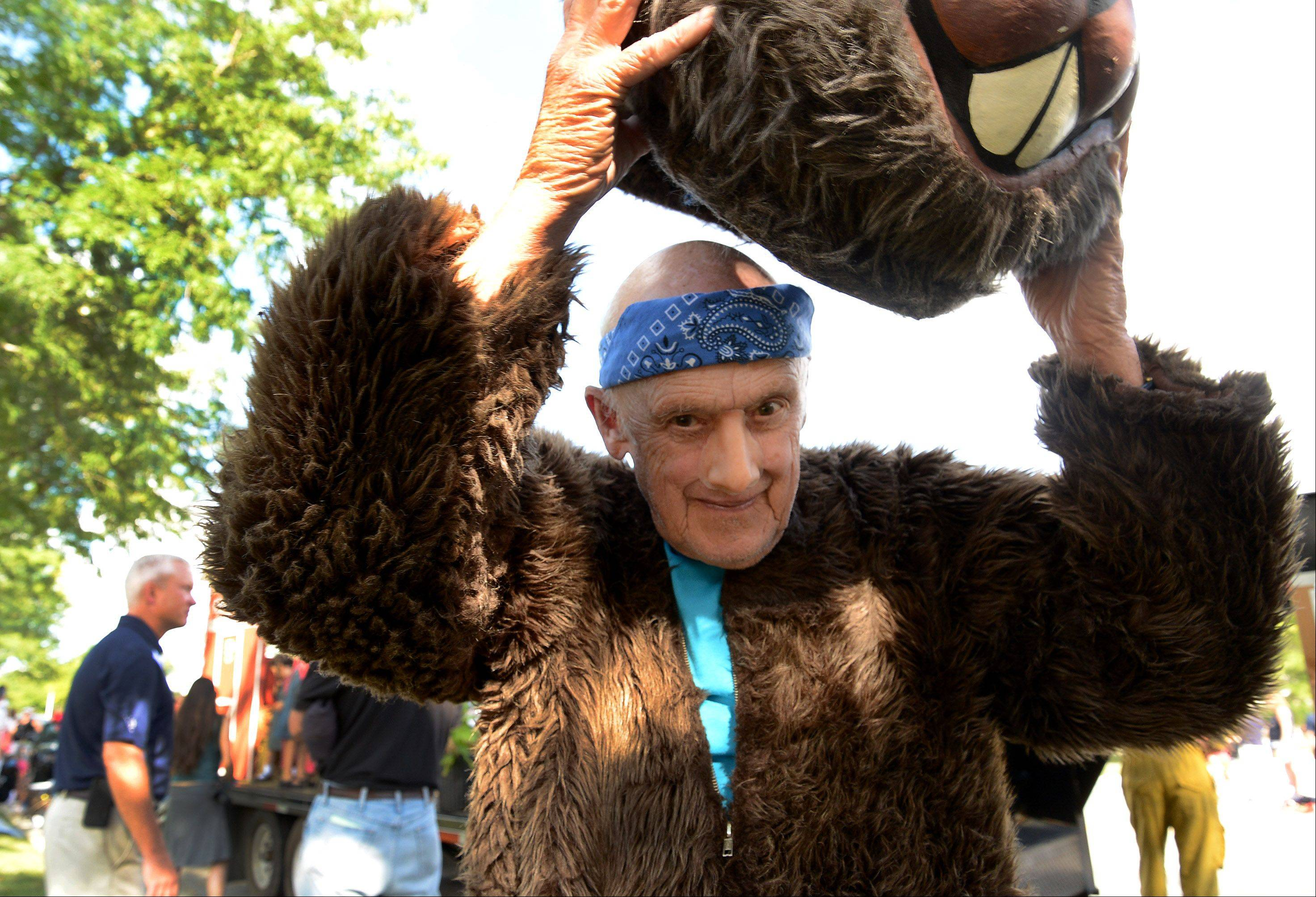 Pete Gigous of the Spring Valley Nature Center slips on the rest of his woodchuck costume Monday before climbing aboard the center's float.