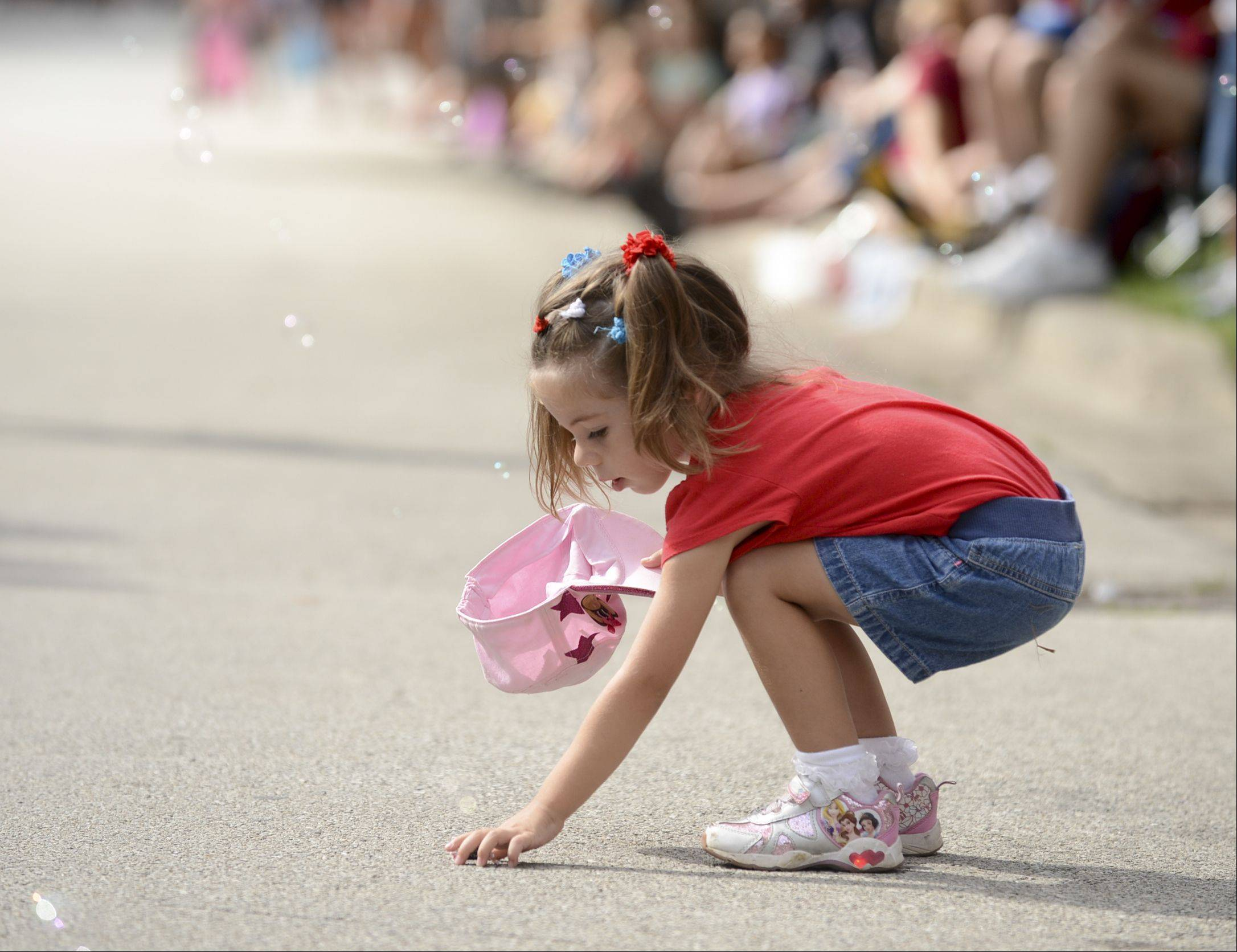 Cherish Kramer, 3, of Glen Ellyn scoops up candy during Naperville's Labor Day parade.
