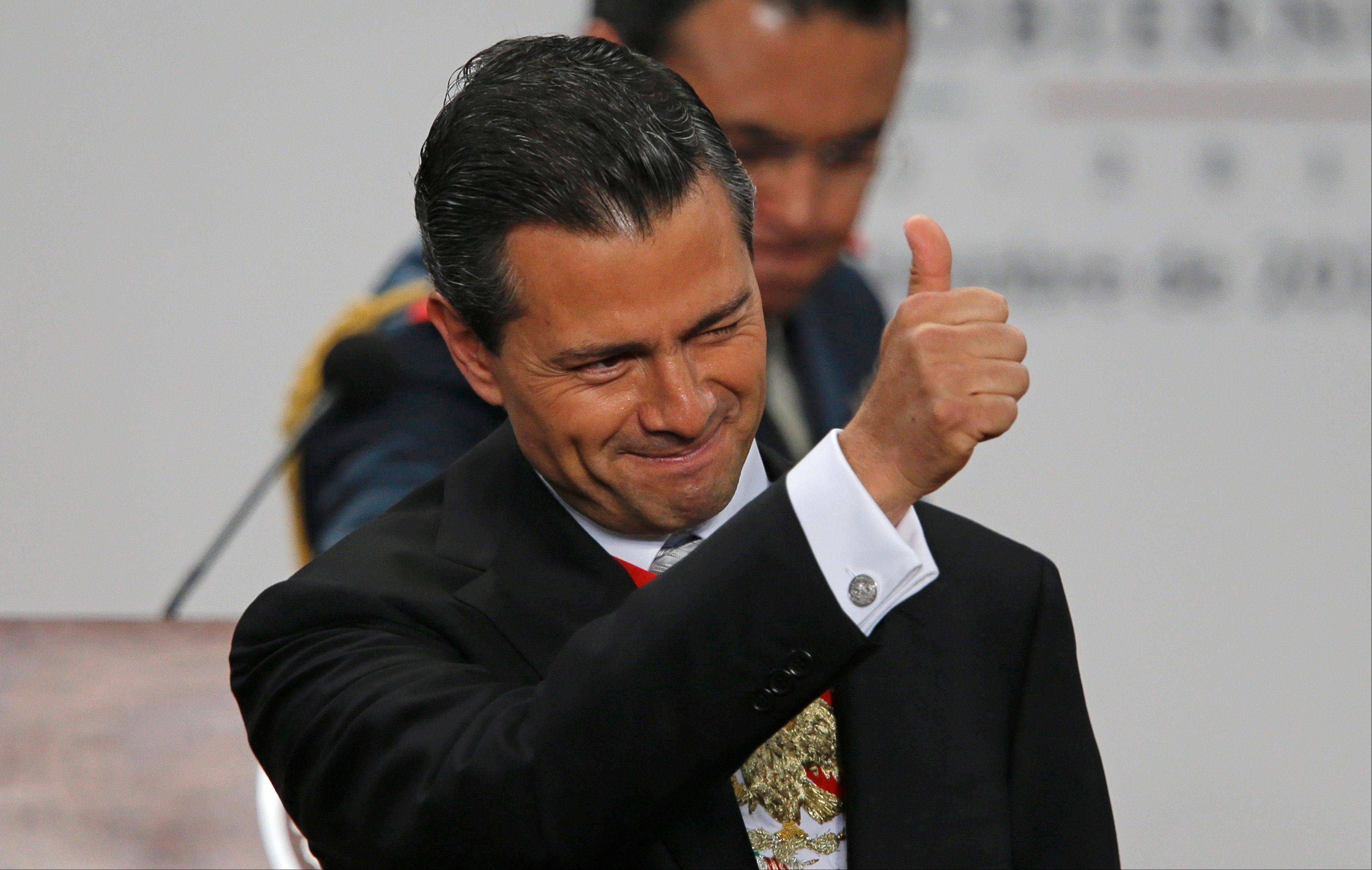 Mexico's President Enrique Pena Nieto gives a thumbs up as he gives his first state-of-the-nation address at Los Pinos presidential residence in Mexico City, Monday, Sept. 2, 2013. Pena Nieto opened his address by praising the passage of a key education reform just hours earlier.
