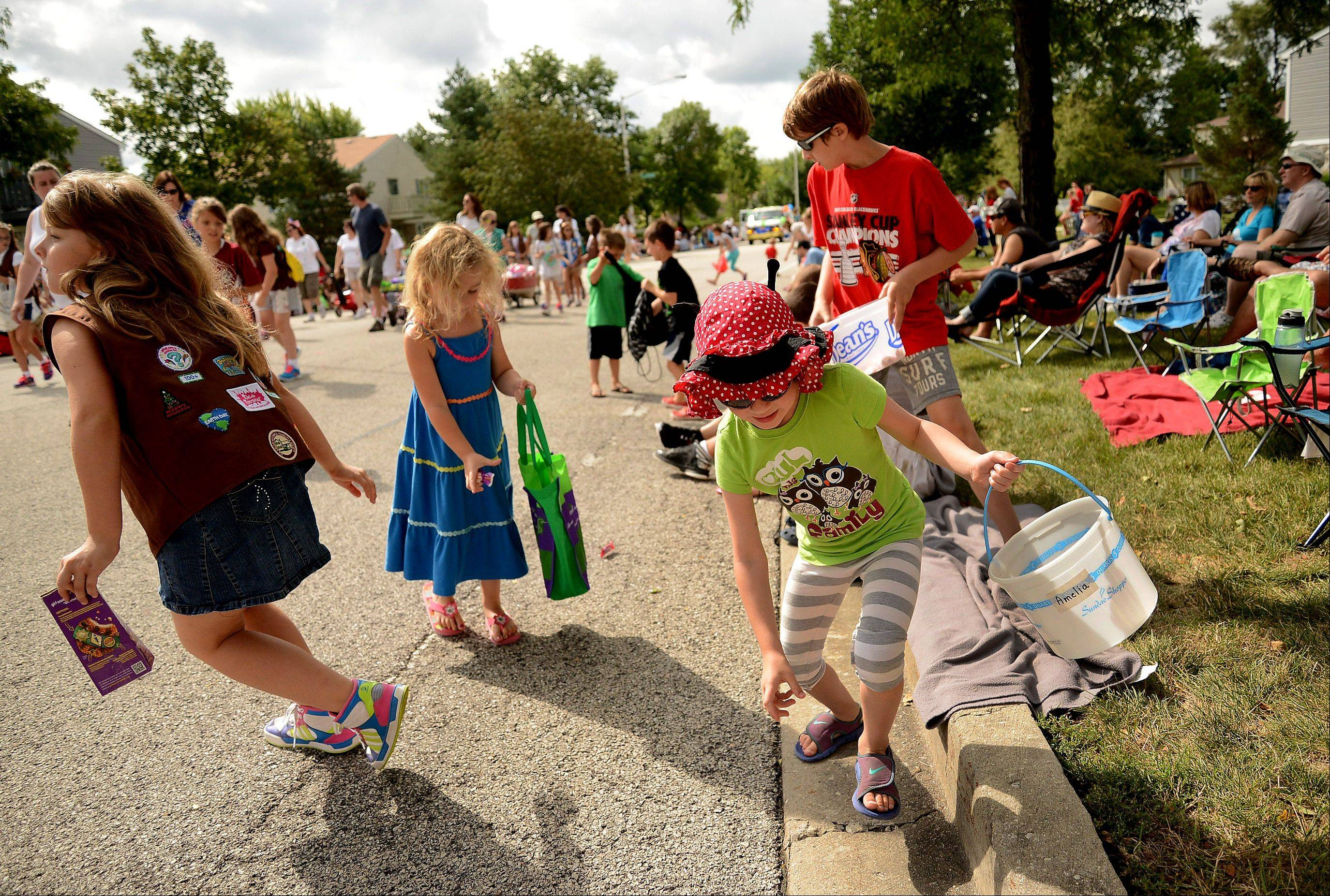 4-year-old Amelia Kozial, right, chases after some candy along the parade route during the annual Schaumburg Septemberfest parade.