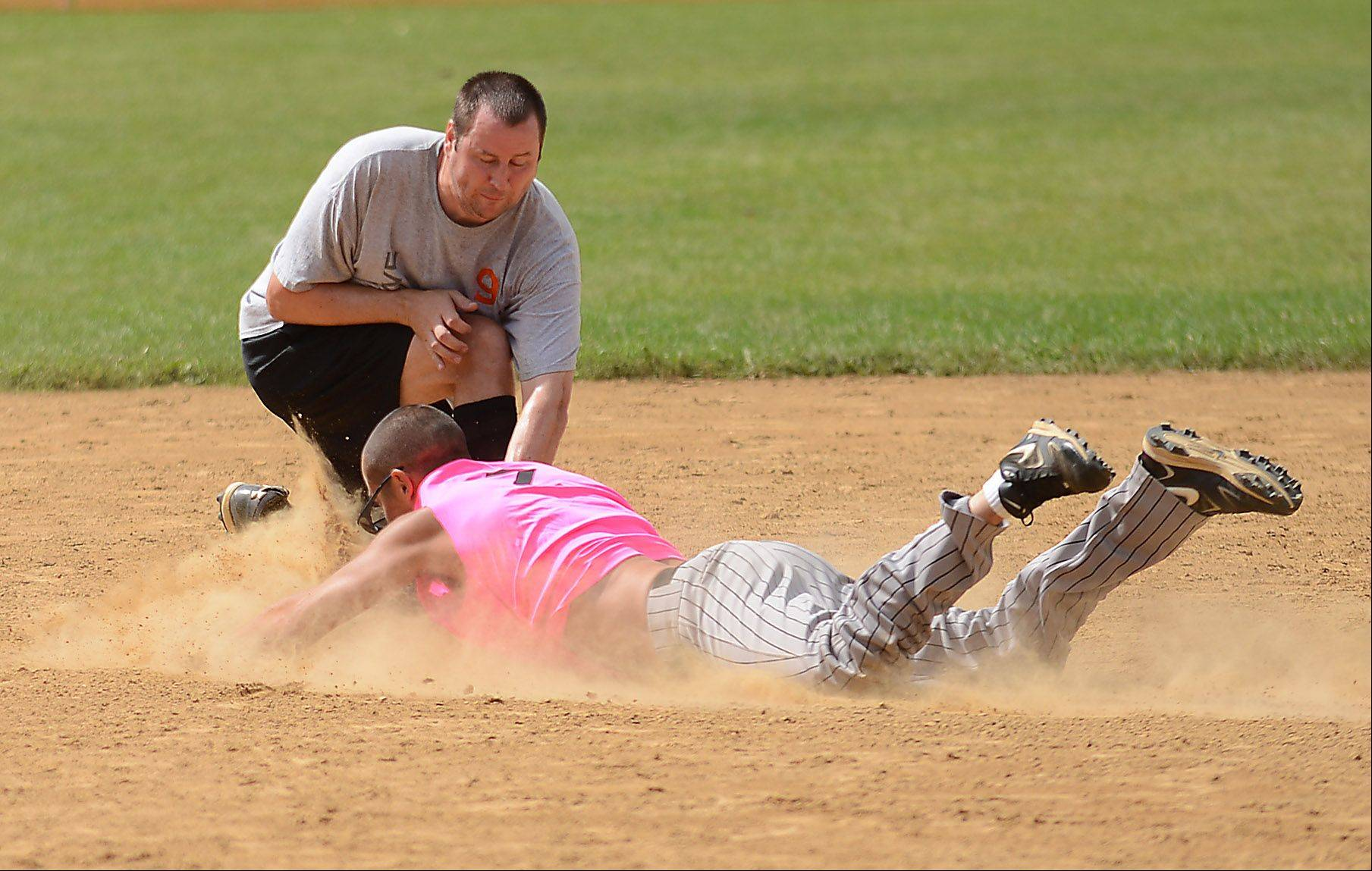 Tyler Burke of the World Famous Pizza team slides safely into second base in front of the tag of Mike Boehnke of R3 Creative during the slow pitch softball tournament that wraps up Maple Park's annual Fun Fest Monday.