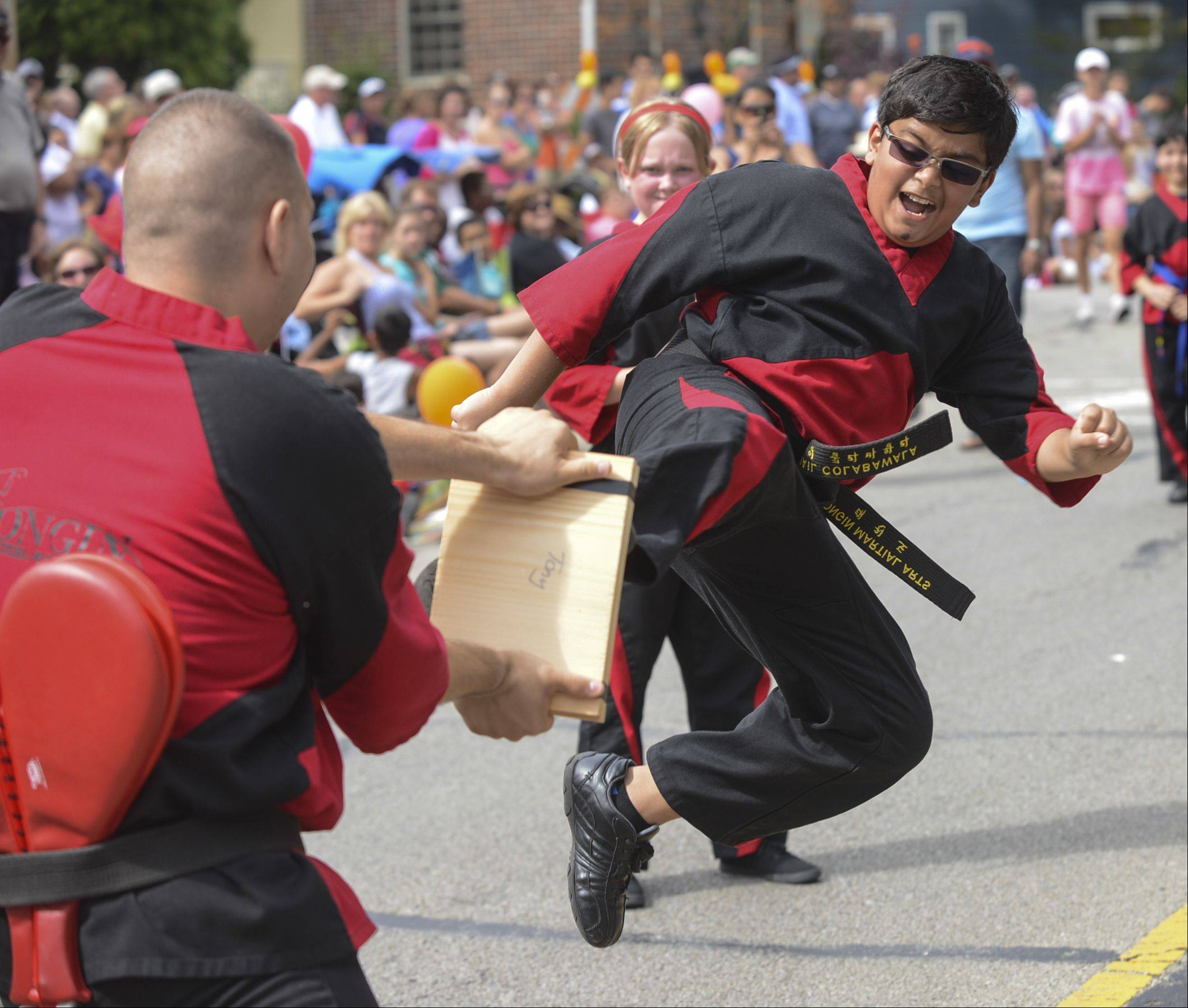 Yongin Martial Arts student Kumail Colabawala, 12 of Naperville does a flying kick in an attempt to break two boards while marching in the Naperville Labor Day parade Monday.