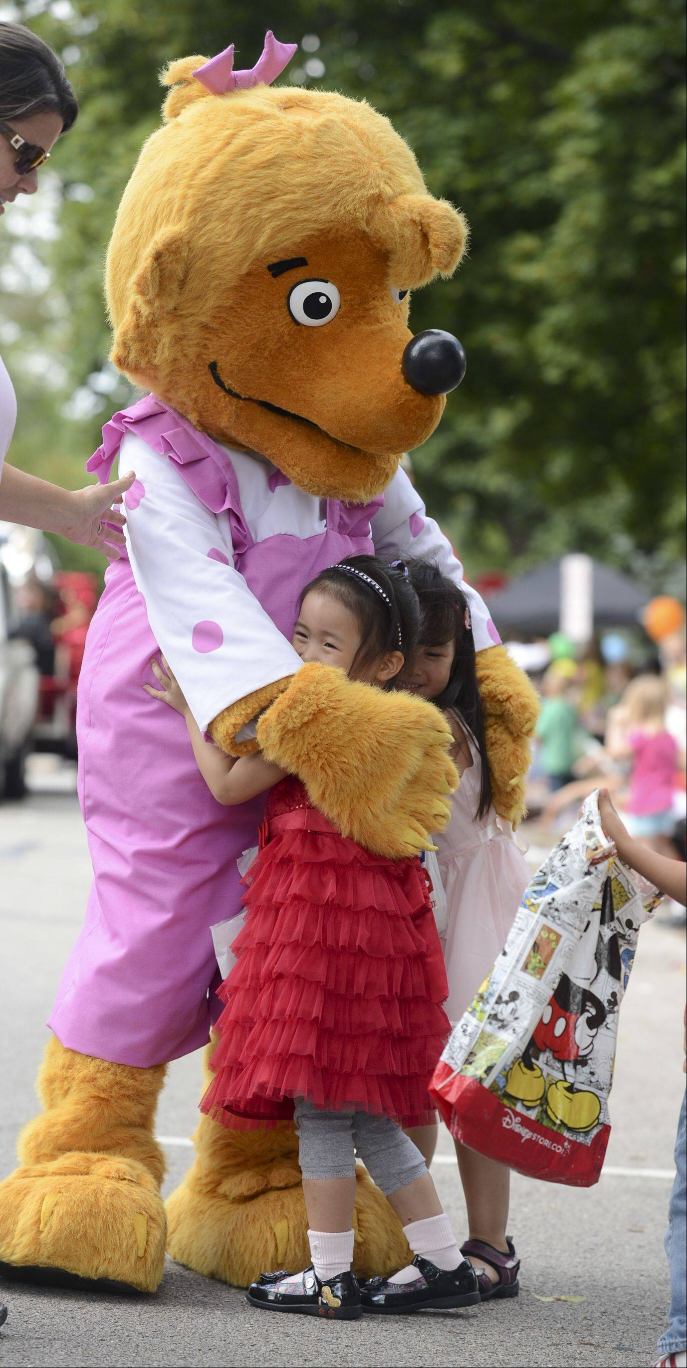 "Sydney Sun and Annabelle Ching both 4 of Naperville give ""Sister Bear"" a big hug during Naperville Labor Day parade Monday."