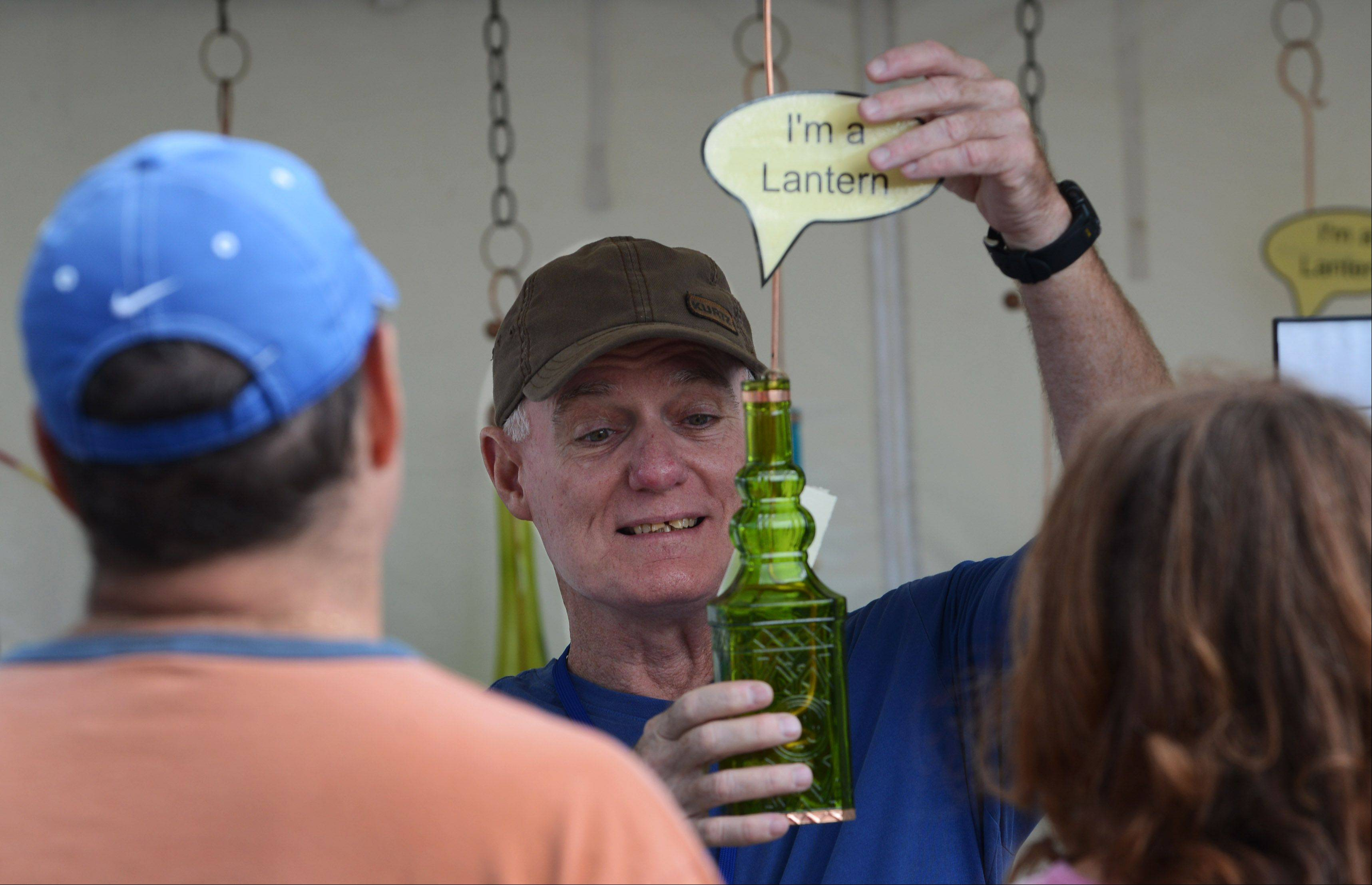Artist Paul Van Duyn of Anderson, Ind. shows his lantern and bird feeders made out of bottles at the 59th Annual Art Fair on the Square on Monday in downtown Lake Forest.