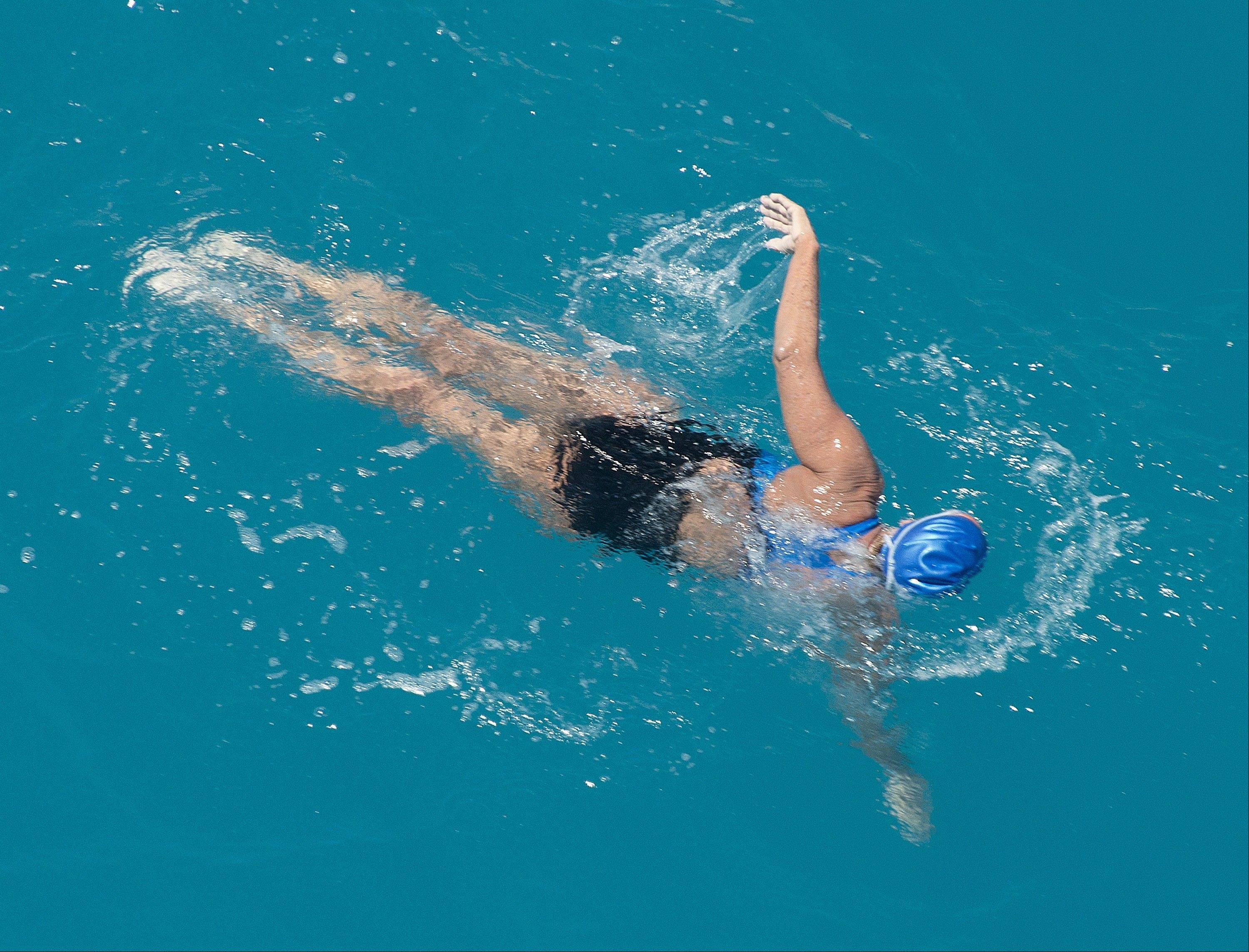 In this photo provided by the Florida Keys News Bureau, Diana Nyad, positioned about two miles off Key West, Fla., Monday, Sept. 2, 2013, swims towards the completion of her 111-mile trek from Cuba to the Florida Keys.