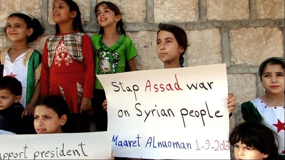 In this Sunday, Sept. 1, 2013, citizen journalism image provided by Edlib News Network, ENN, which has been authenticated based on its contents and other AP reporting, Syrian children hold signs during a demonstration in Maaret al-Numan, Idlib province, northern Syria. More than 100,000 Syrians have been killed since an uprising against Syrian President Bashar Assad erupted in 2011.