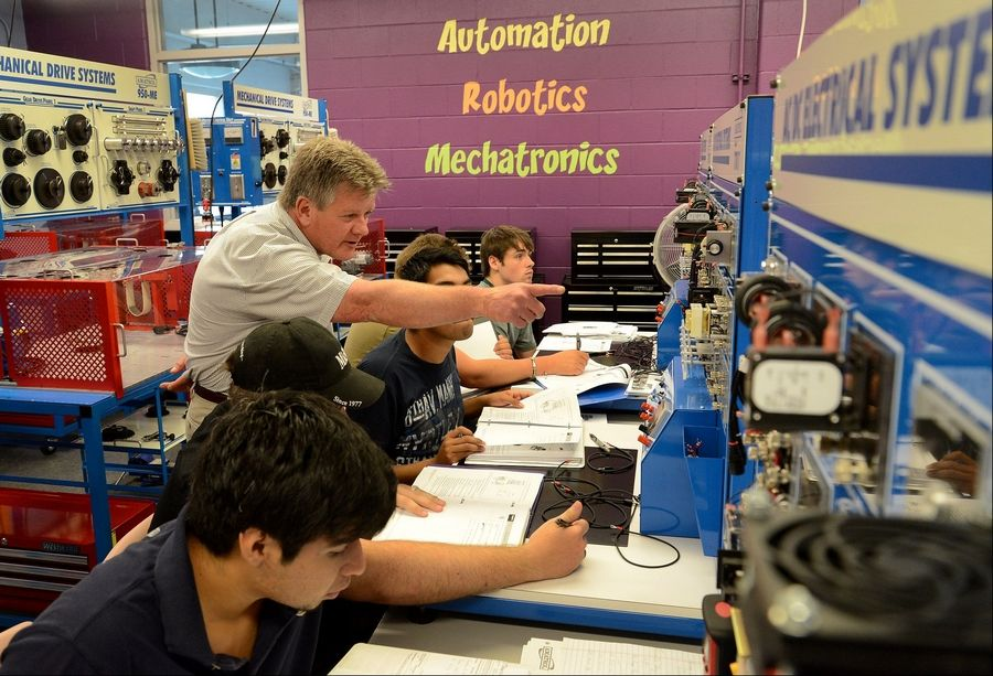 College of Lake County Dean Emeritus Gary Morgan instructs pupils about mechatronics. The new field blends mechanics, electronics and software.