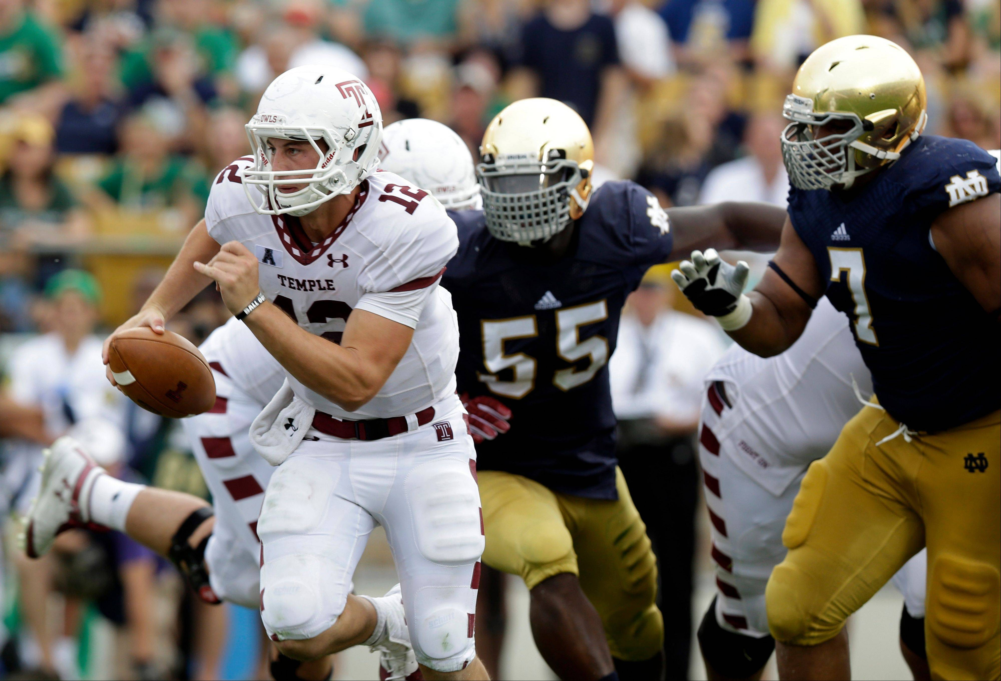 Temple quarterback Connor Reilly scrambles away from Notre Dame's Prince Shembo (55) and Stephon Tuitt during the first half of Saturday's game in South Bend, Ind.