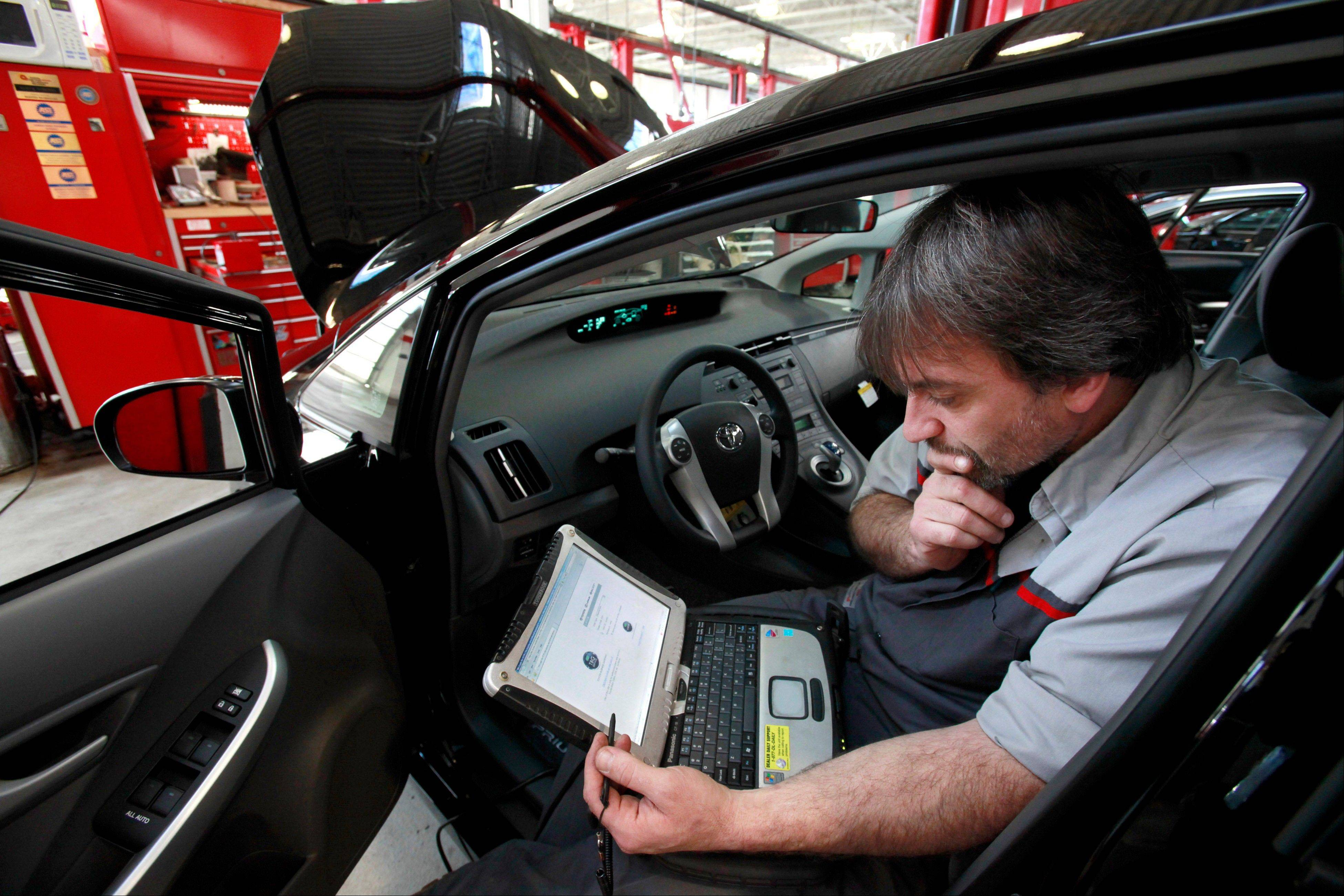 Master diagnostic technician Kurt Juergens uses a laptop computer to diagnose and repair the brake system on a 2010 Toyota Prius in the repair shop of a Toyota dealership in Norwood, Mass.