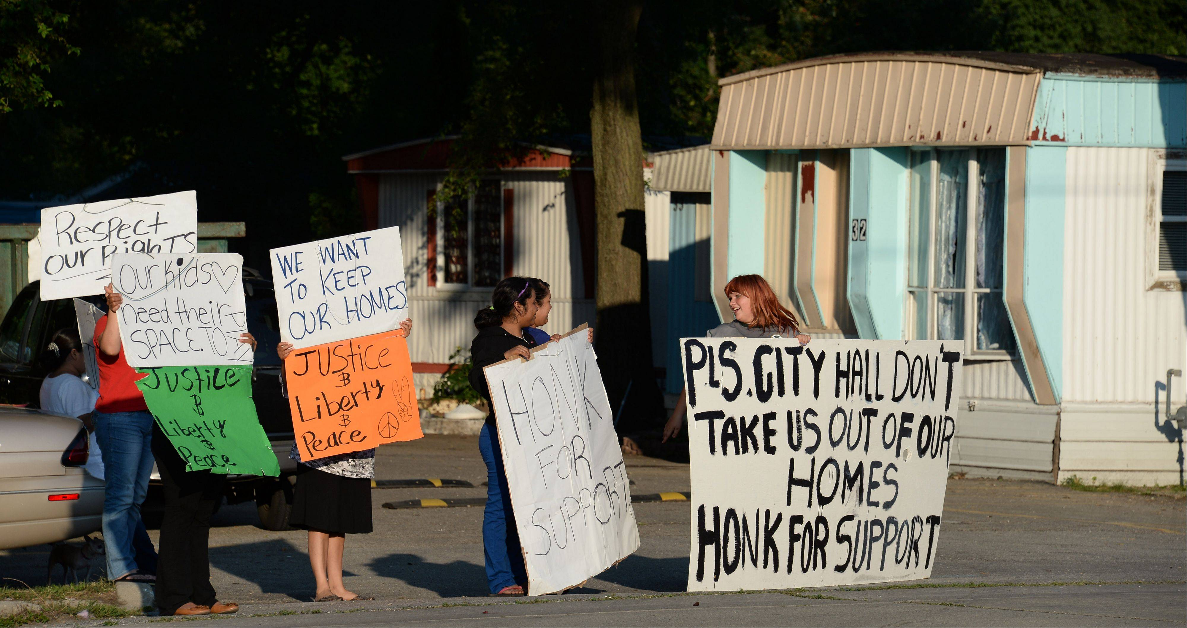 Ellen Piotrowski, 13, of Wheeling, right, who lives in the Fox Point community on Milwaukee Avenue, protests with her neighbors Aug. 16. �