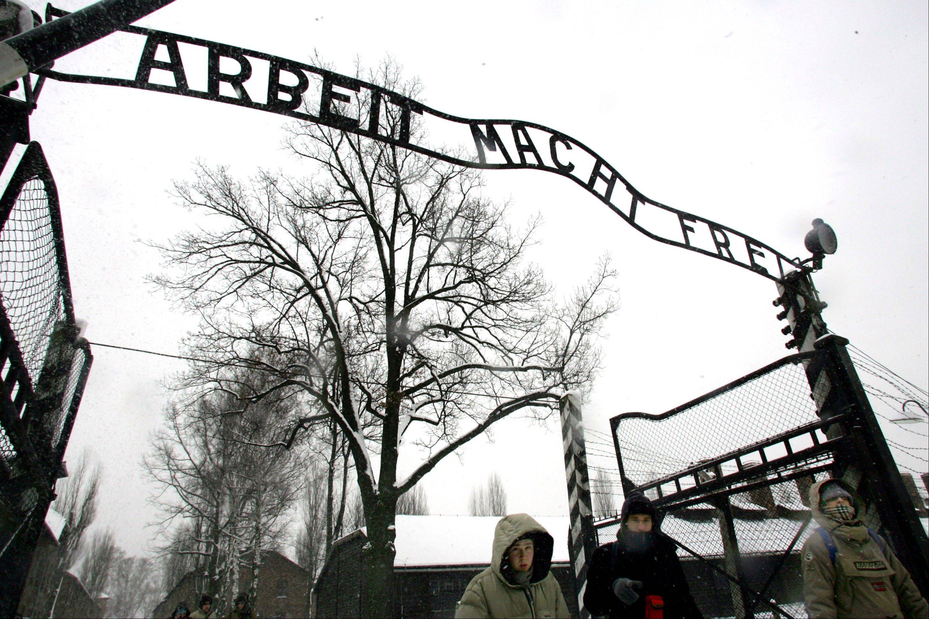 "Visitors walk under the notorious ""Arbeit Macht Frei"" sign at the entrance gate of the Auschwitz Nazi concentration camp in Oswiecim, southern Poland."