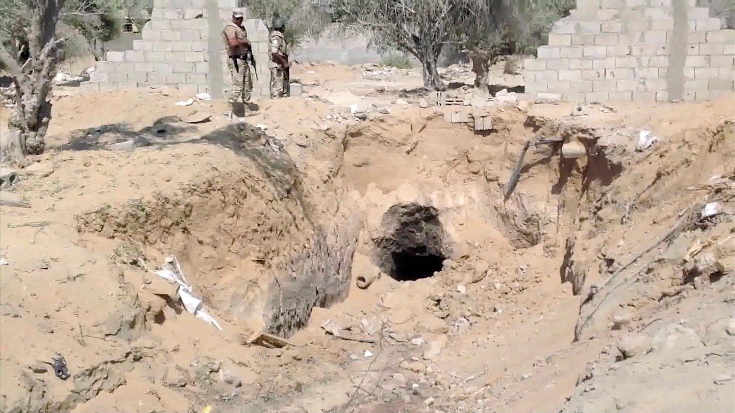 Egyptian Army personnel supervise the destruction of tunnels between Egypt and the Gaza Strip at the border, near the town of Rafah, northern Sinai, Tuesday. Tunnels between Egypt and the Gaza have been used to smuggle everything from weapons, to cigarettes and fuel but now the Egyptian military appears determined to close the tunnels once and for all.