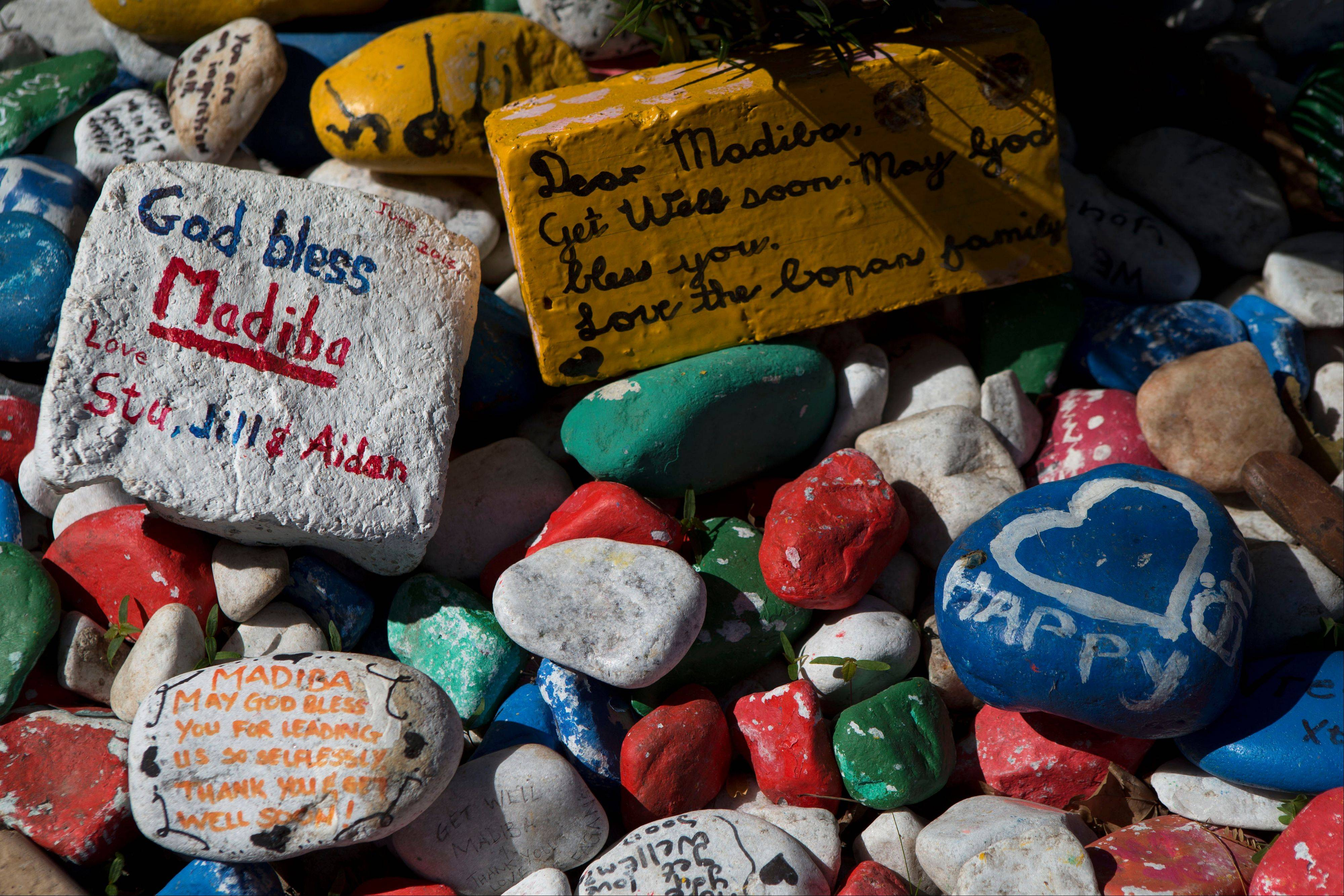 Stones painted with messages of support from well-wishers sit outside the residence of former South African President Nelson Mandela, where Mandela was continuing to receive medical care after leaving the hospital.
