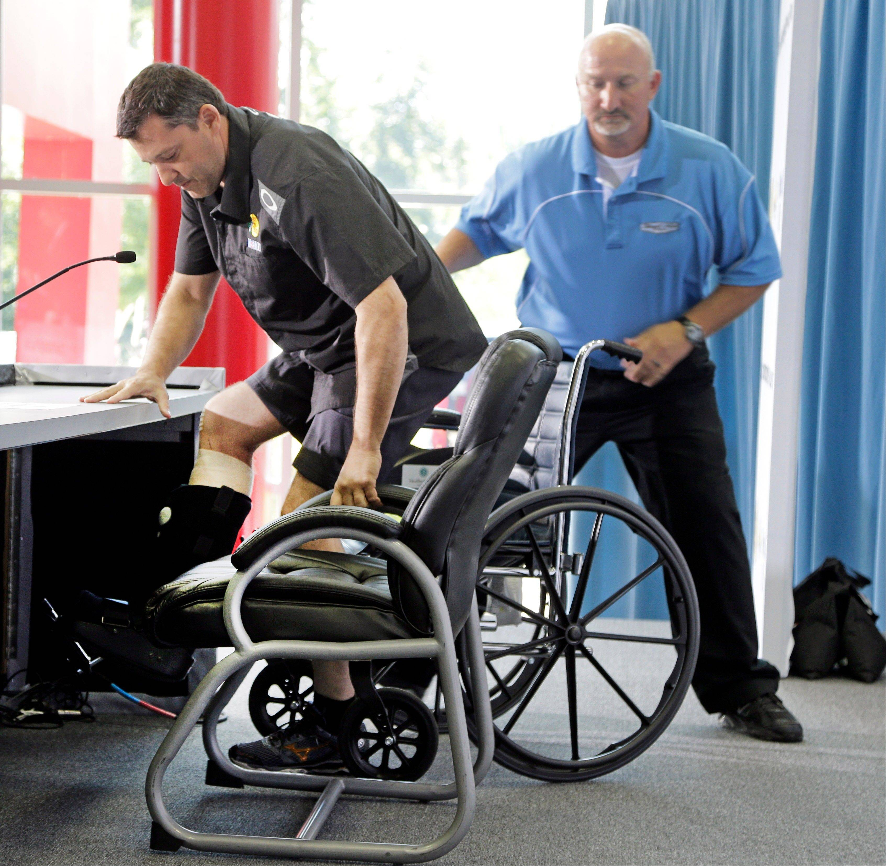 NASCAR driver and team co-owner Tony Stewart, left, arrives in a wheelchair assisted by Josh Katz, right, before a news conference at Stewart-Haas Racing's headquarters in Kannapolis, N.C., Tuesday, Sept. 3, 2013.