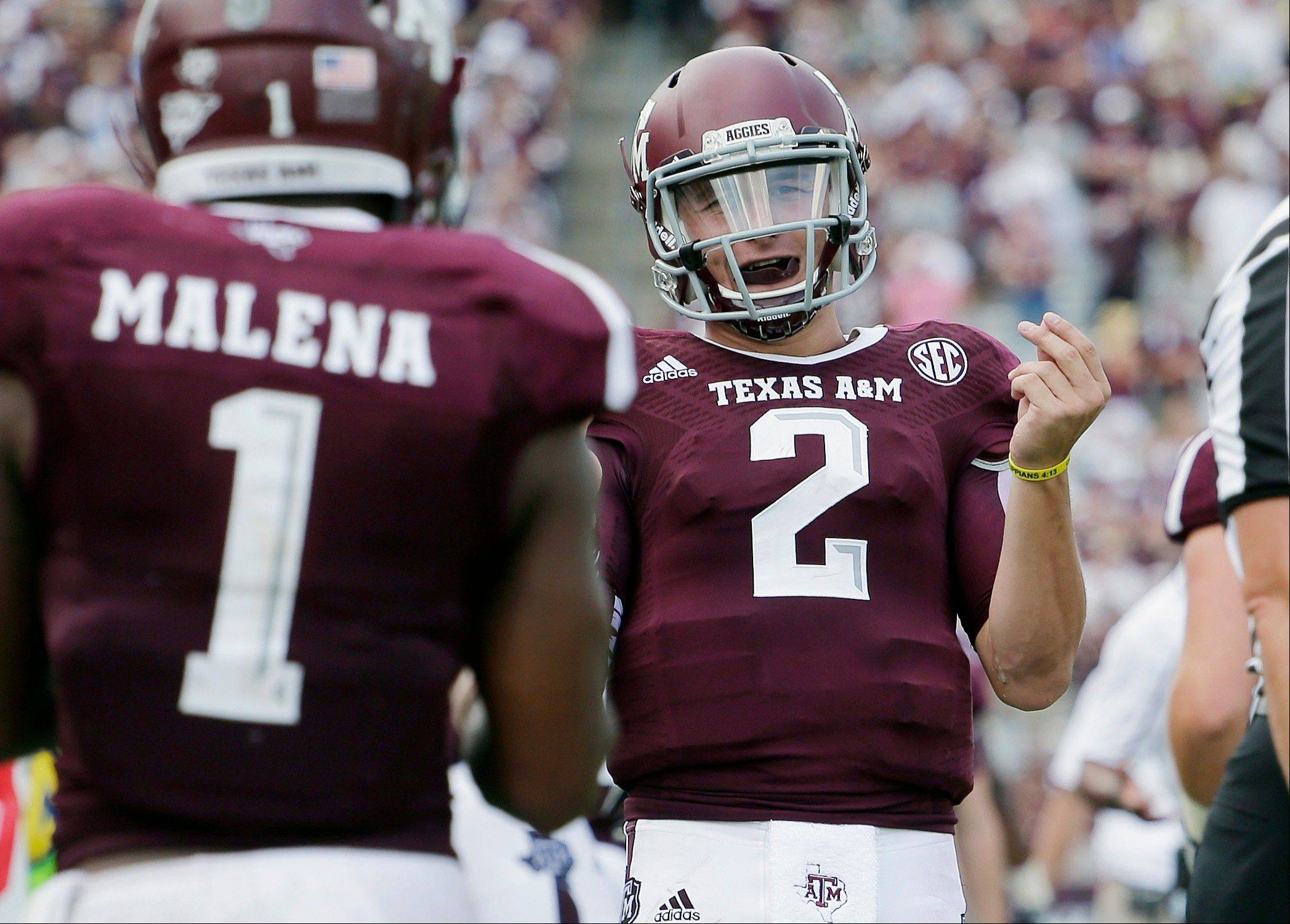 Texas A&M quarterback Johnny Manziel (2) celebrates a touchdown Saturday with teammate Ben Malena (1) during the fourth quarter against Rice.
