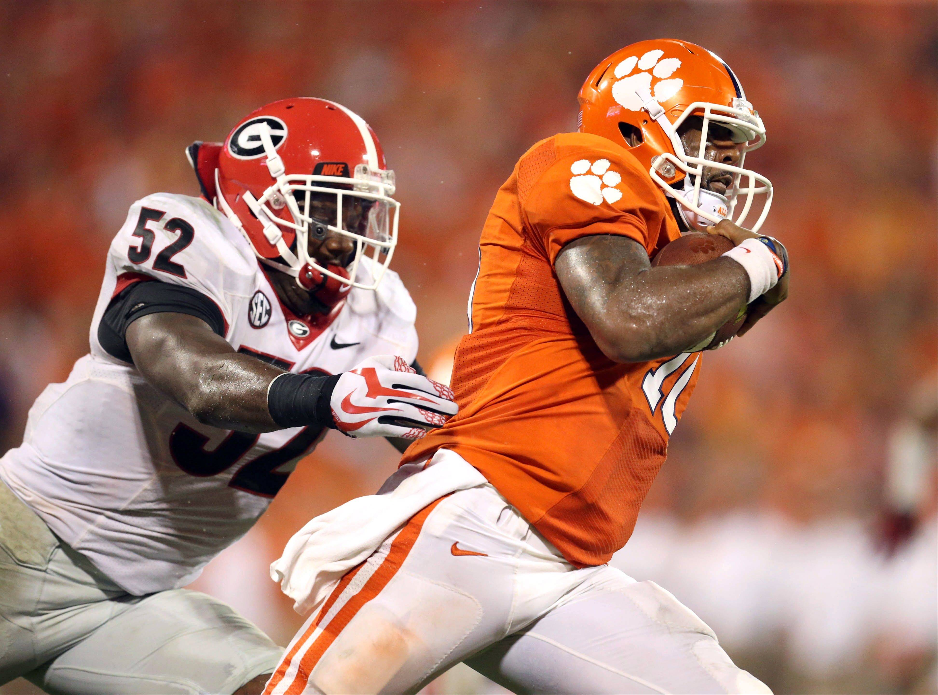 Clemson quarterback Tajh Boyd, right, outruns the tackle of Georgia linebacker Amarlo Herrera, left, Saturday in the second half at Memorial Stadium in Clemson, S.C. Clemson defeated Georgia 38-35.
