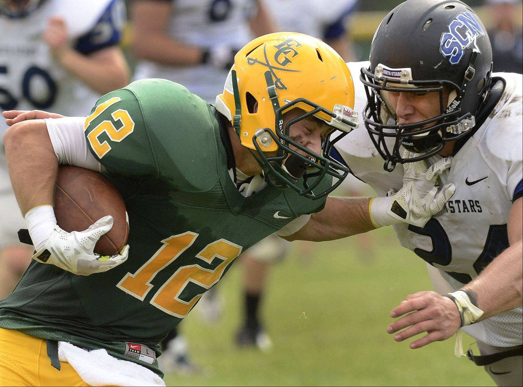 Elk Grove's Matthew Wary hits St. Charles North's Evan Kurtz during Saturday's football game.