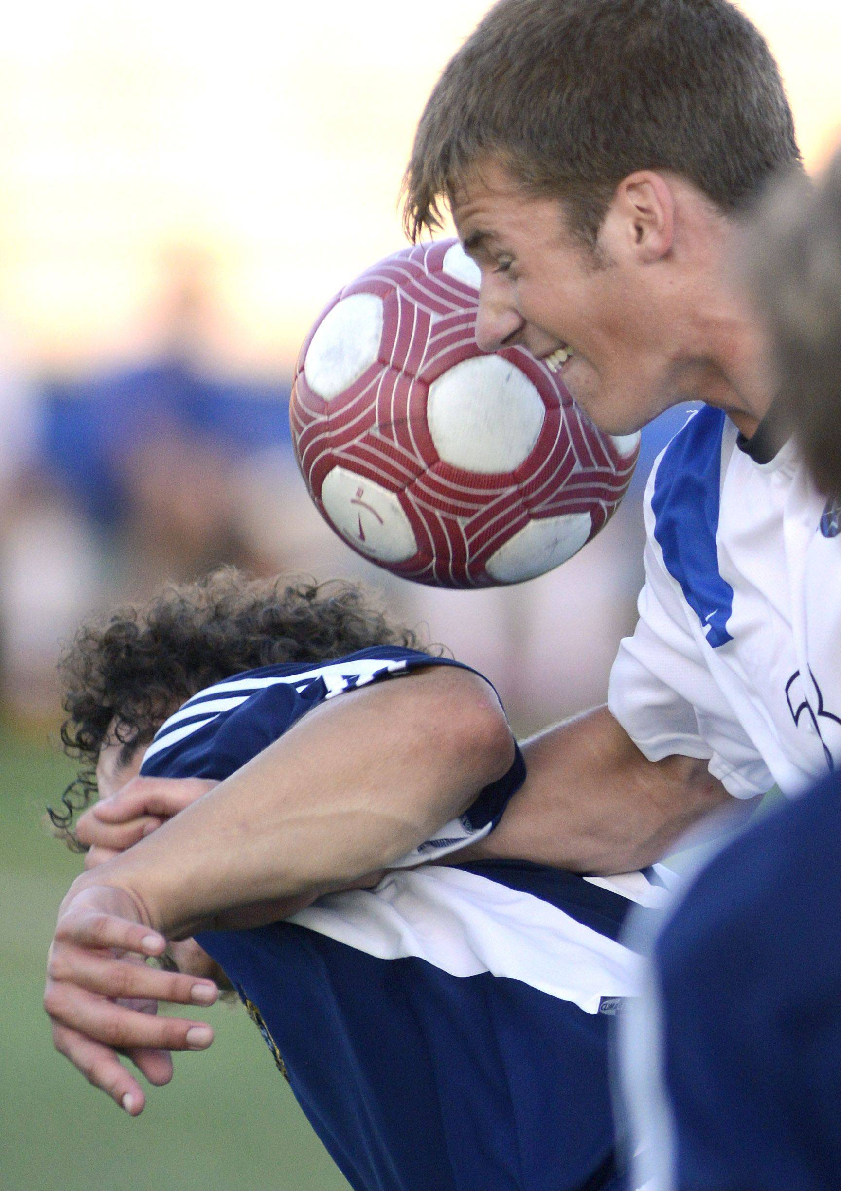 Neuqua Valley's Kersey Dickerson and St. Charles North's Adam Hoffman collide while fighting for the ball during Tuesday's soccer game.