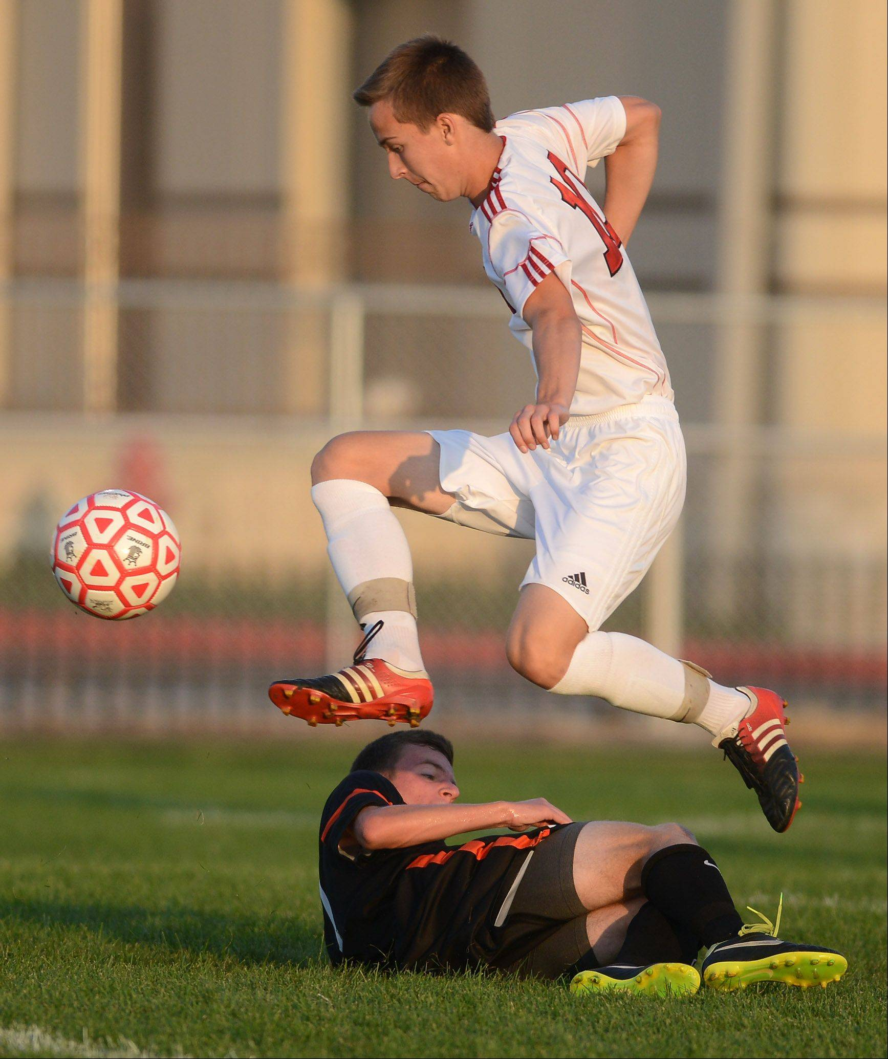 Batavia's Adam Heinz hops over St. Charles East's Jacob Sterling during Thursday's soccer game in Batavia.