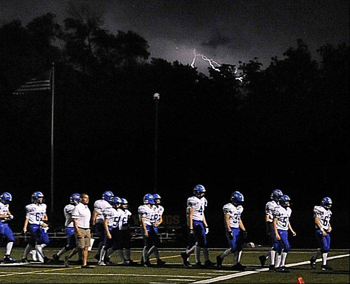Storms linger in the background as Lake Zurich's football team heads off the field in the season opener at Fremd on Friday.