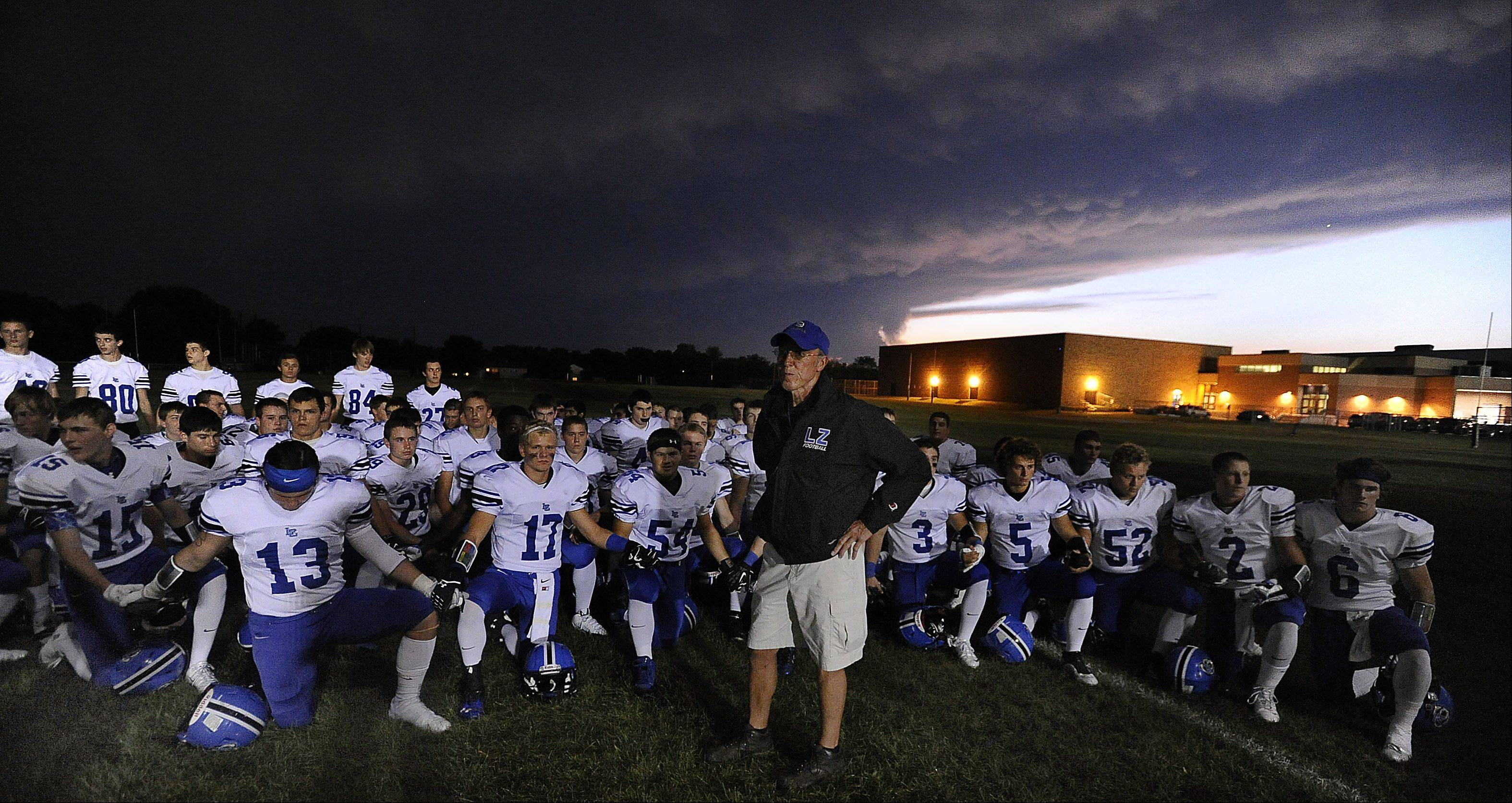 Lake Zurich's head coach Dave Proffitt stands with his players before the game as storm clouds move in on Friday in Palatine.