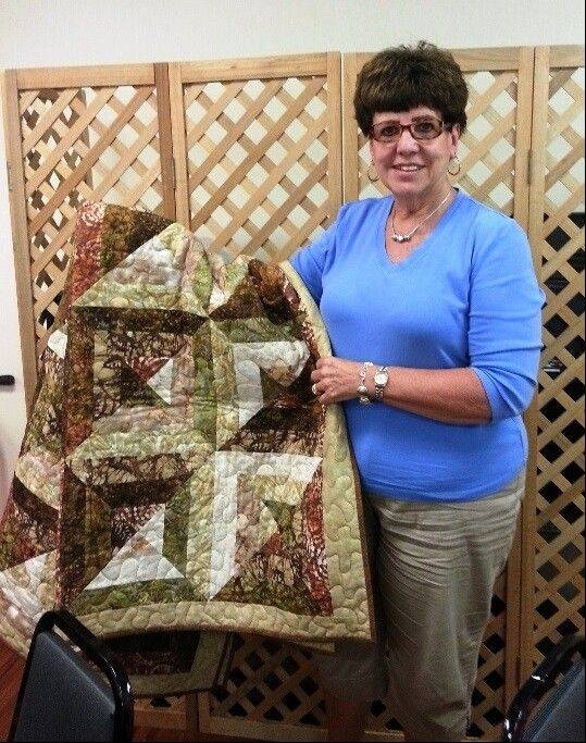 Mickey Farmer with her grand raffle prize, a homemade quilt.