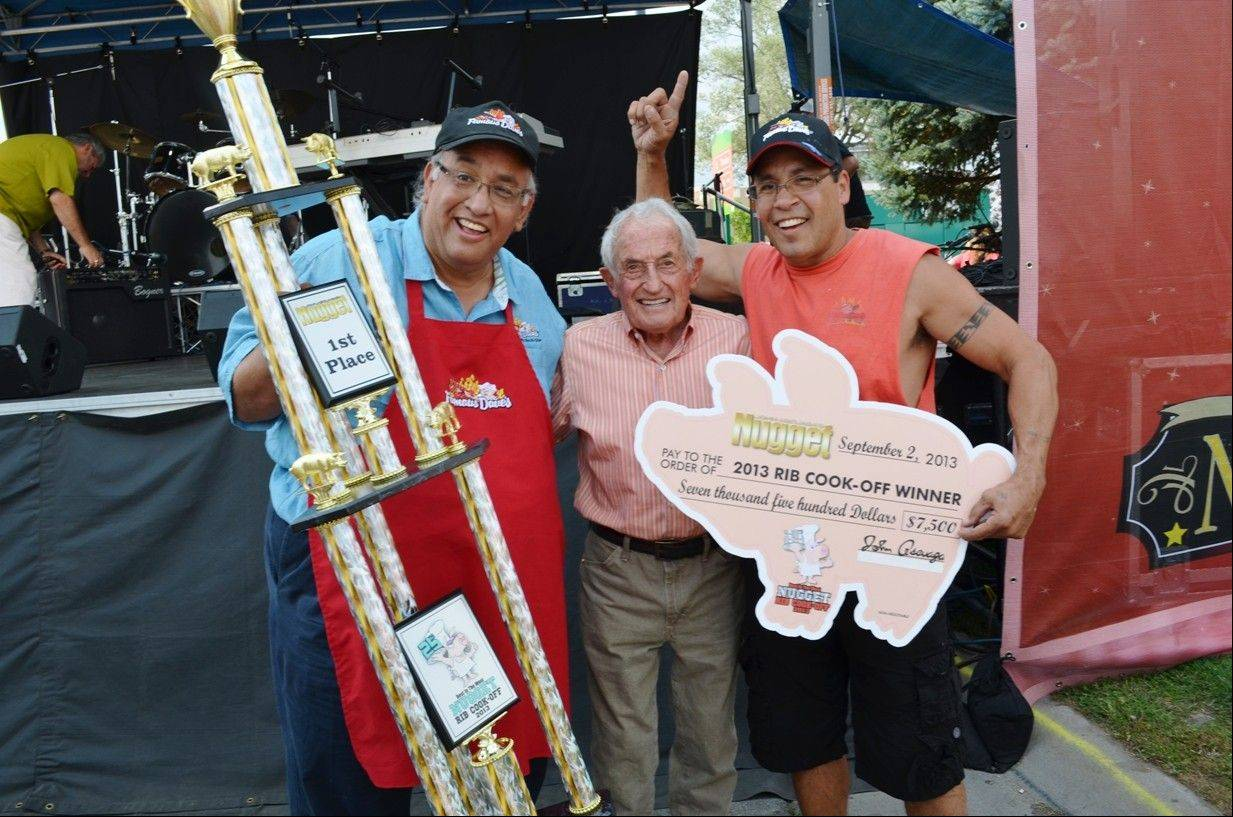Dave Anderson, owner of Famous Dave�s BBQ, left, on Monday accepts the first-place trophy at the 25th annual Best in the West Nugget Rib Cook-Off in Sparks, Nev. from John Ascuaga, owner of John Ascuaga�s Nugget hotel-casino. Famous Dave�s pitmaster Rob Stately is at right.