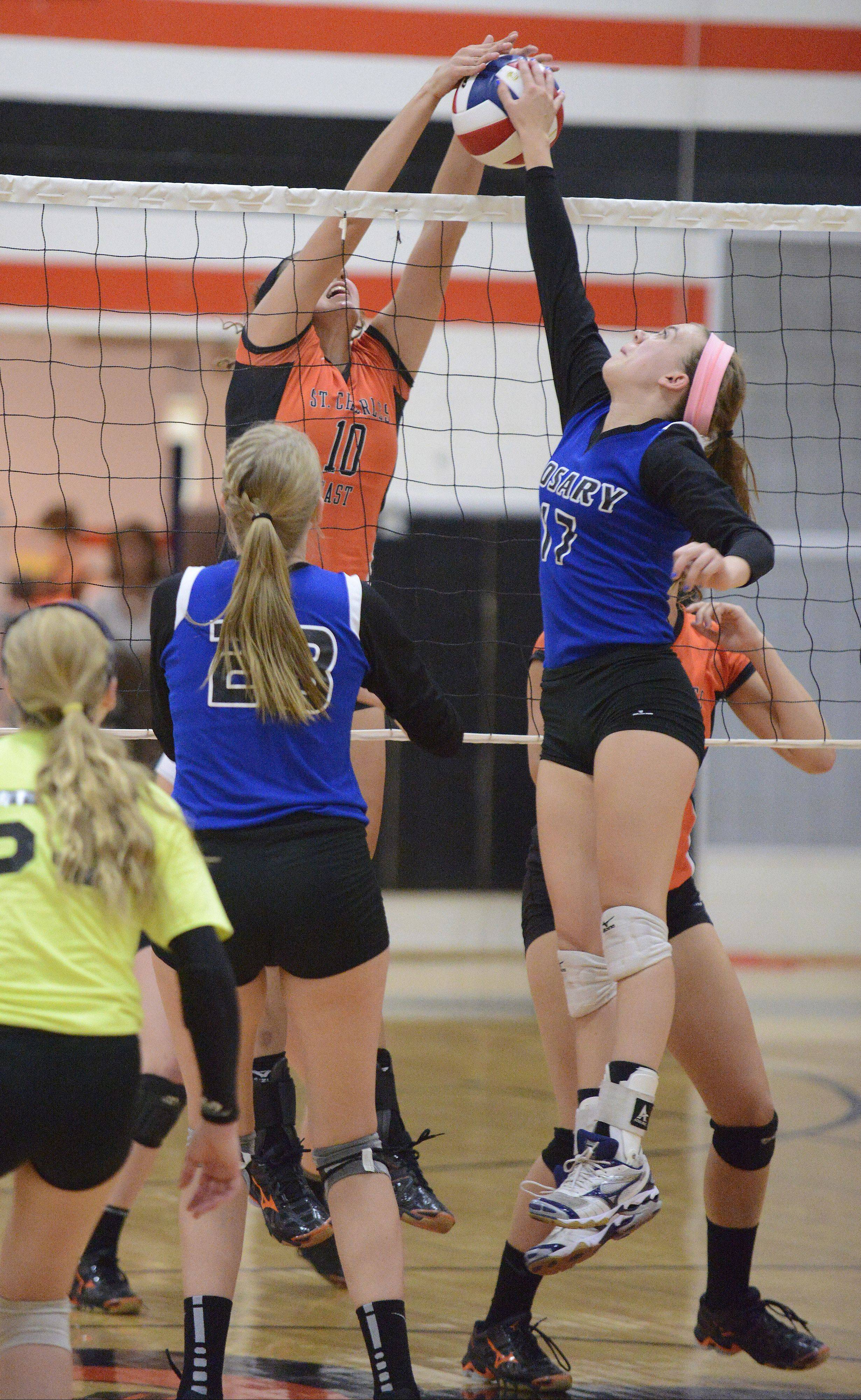 St. Charles East�s Mikaela Mosquera and Rosary�s Grace Konovodoff square off at the net in the third game Wednesday in St. Charles. Rosary�s Michaela Ping is pictured on the left.