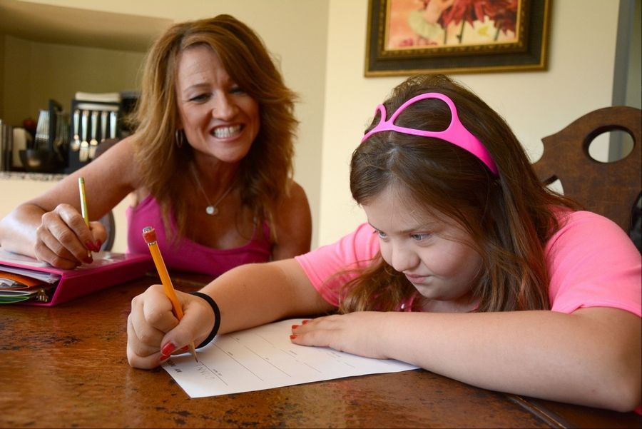 Nancy Gianni, left, helps daughter GiGi work on homework at their home in South Barrington.