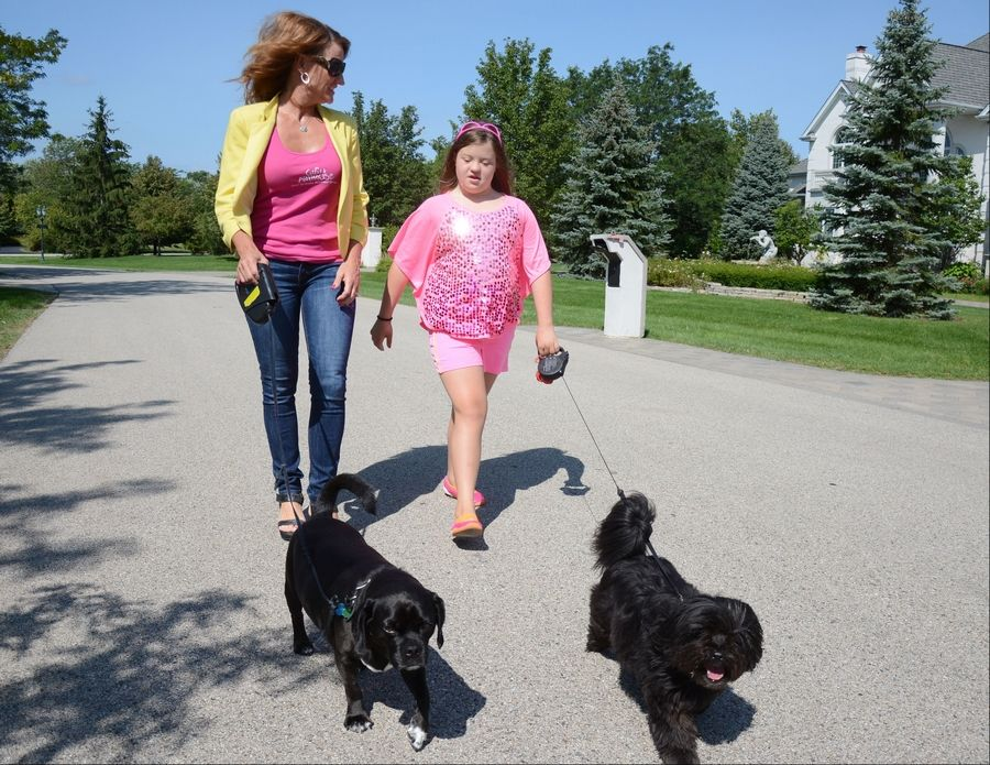 Nancy Gianni, left, and daughter GiGi walk their dogs in their South Barrington neighborhood.