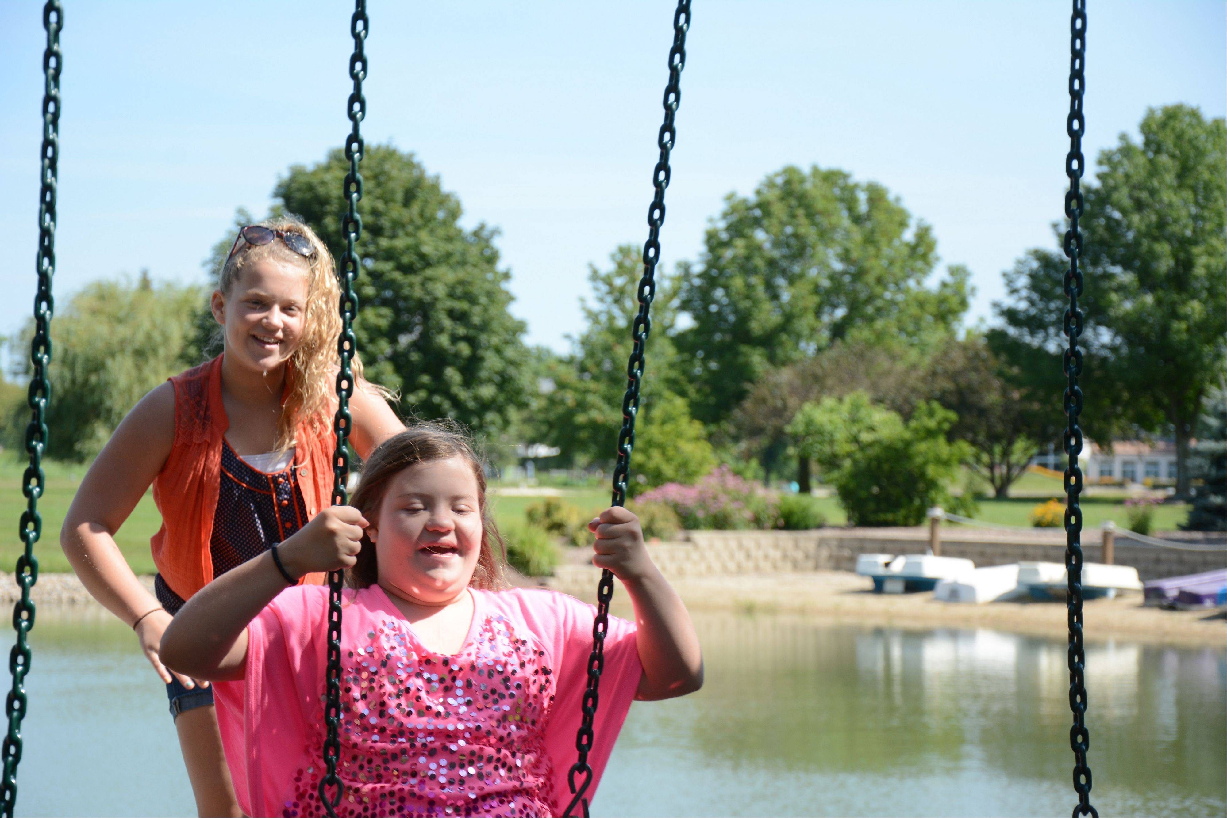 Bella Gianni, background, pushes her sister GiGi on a swing at a park near their home in South Barrington.