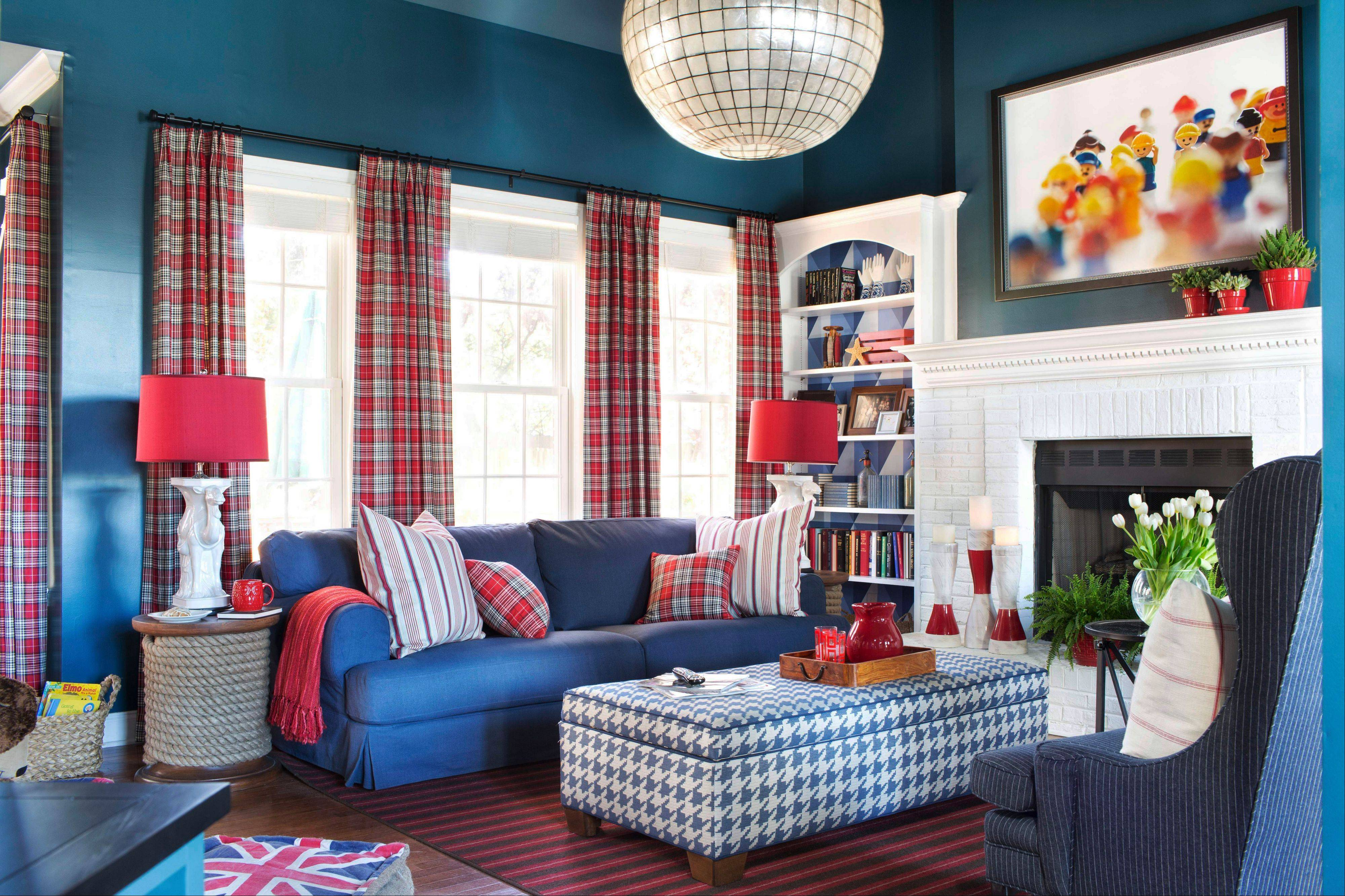 A playful family room is decorated by designer Brian Patrick Flynn with framed photography of Dupo figures from the 1980s, playful accessories and a bold palette of navy blue and fire engine red.