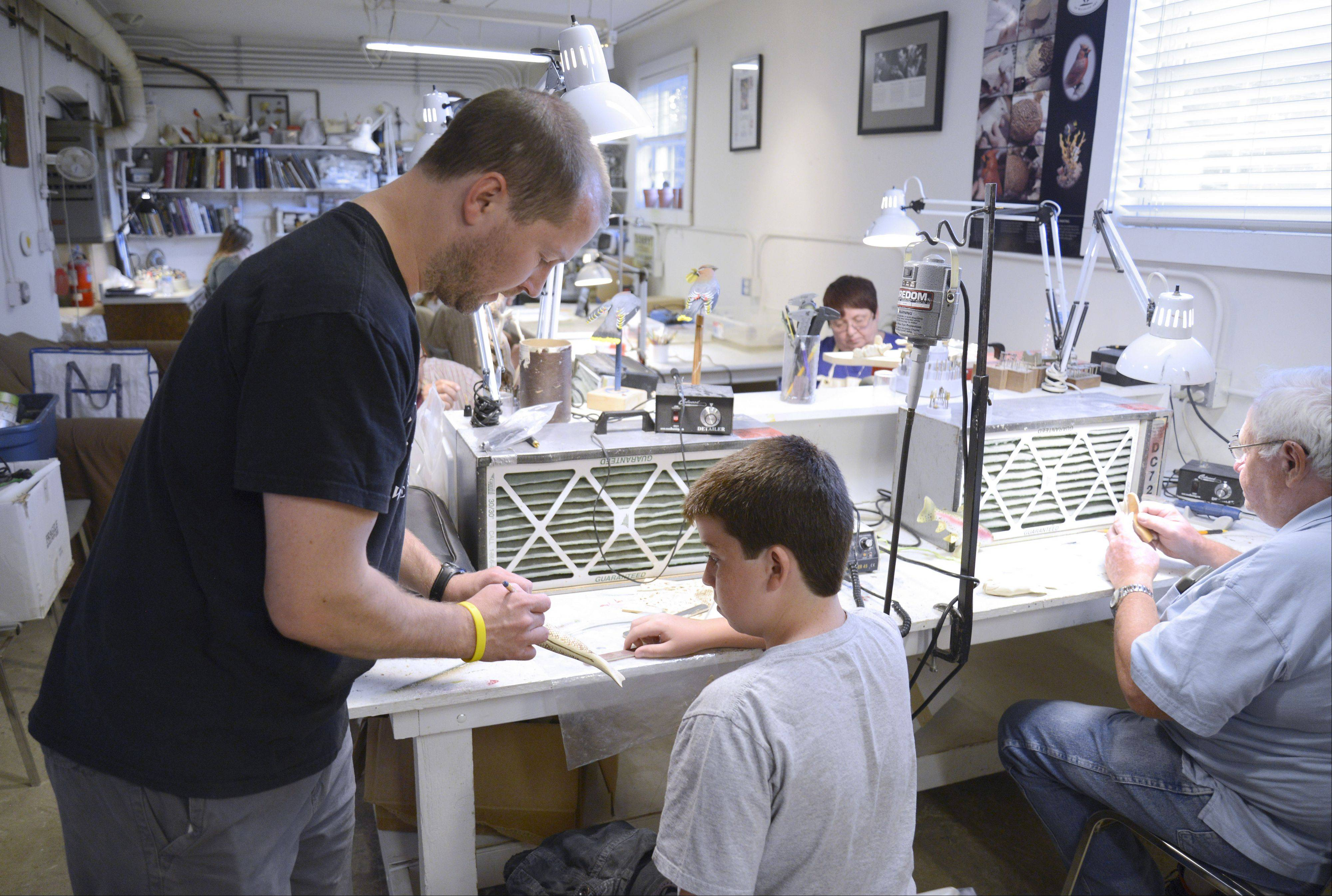 Josh Guge of the Guge Institute of Wildlife Art in Gilberts works with student Shane Cloonan, 12, of Elgin. Though he took up wood carving only about eight months ago, Shane already has established himself as one of the nation's best in his age group.