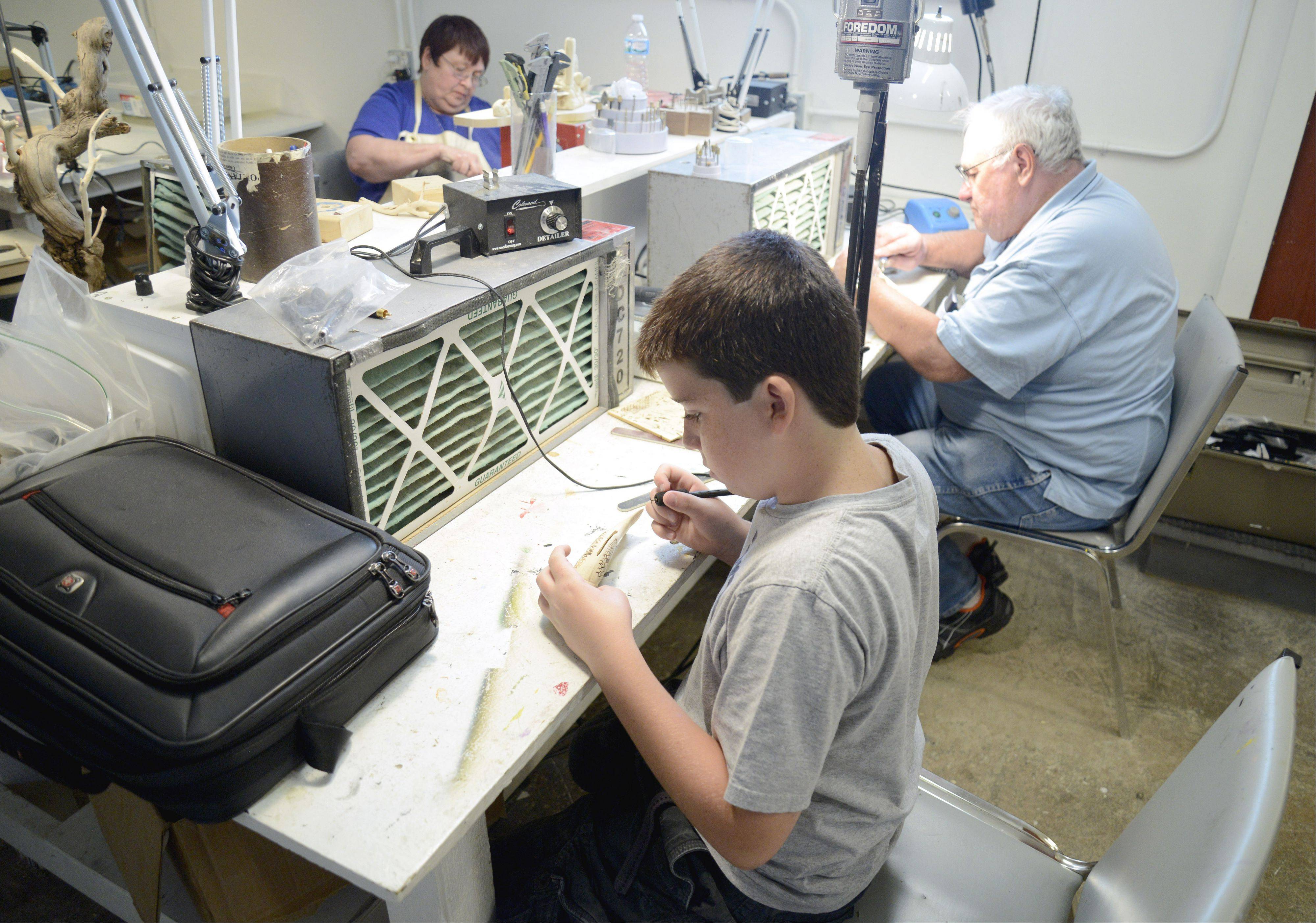 Shane Cloonan, 12, of Elgin works on a new carving of a smallmouth bass during class at the Guge Institute of Wildlife Art in Gilberts. Though he took up wood carving only about eight months ago, Shane already has established himself as one of the nation's best in his age group.