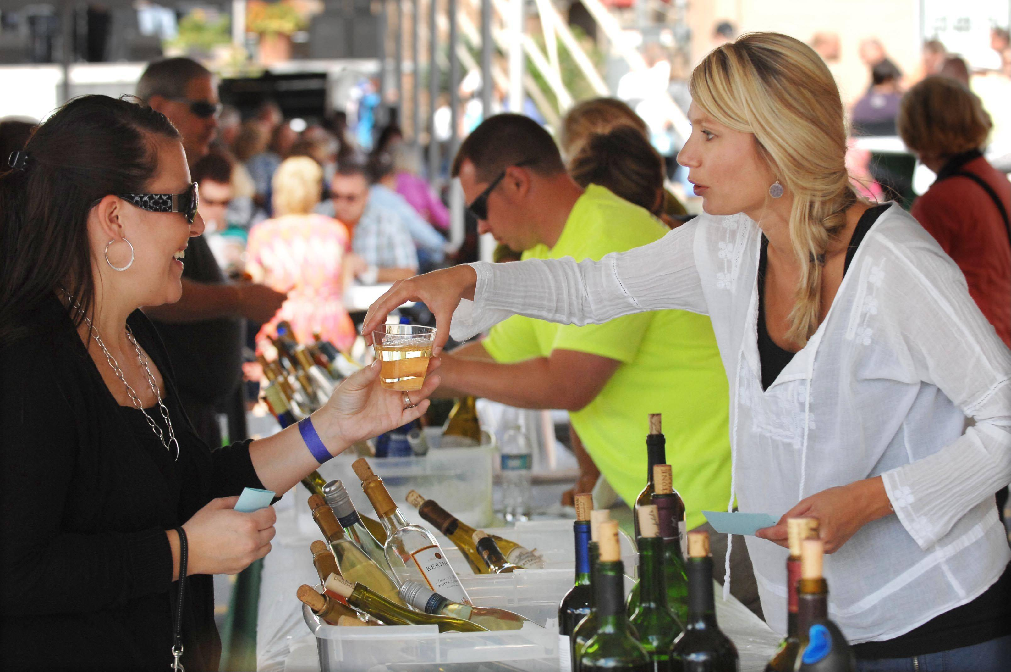 Natalya Villa serves wine at last year's Festival of the Vine in downtown Geneva. Visitors to the wine and food tents first must purchase tickets, $1 each, which they can use to buy wine and food.