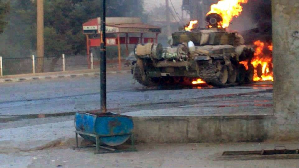 In this citizen journalism image provided by The Syrian Revolution against Bashar Assad which has been authenticated based on its contents and other AP reporting, a Syrian military tank burns Wednesday during clashes with Free Syrian army fighters in Joubar a suburb of Damascus, Syria.